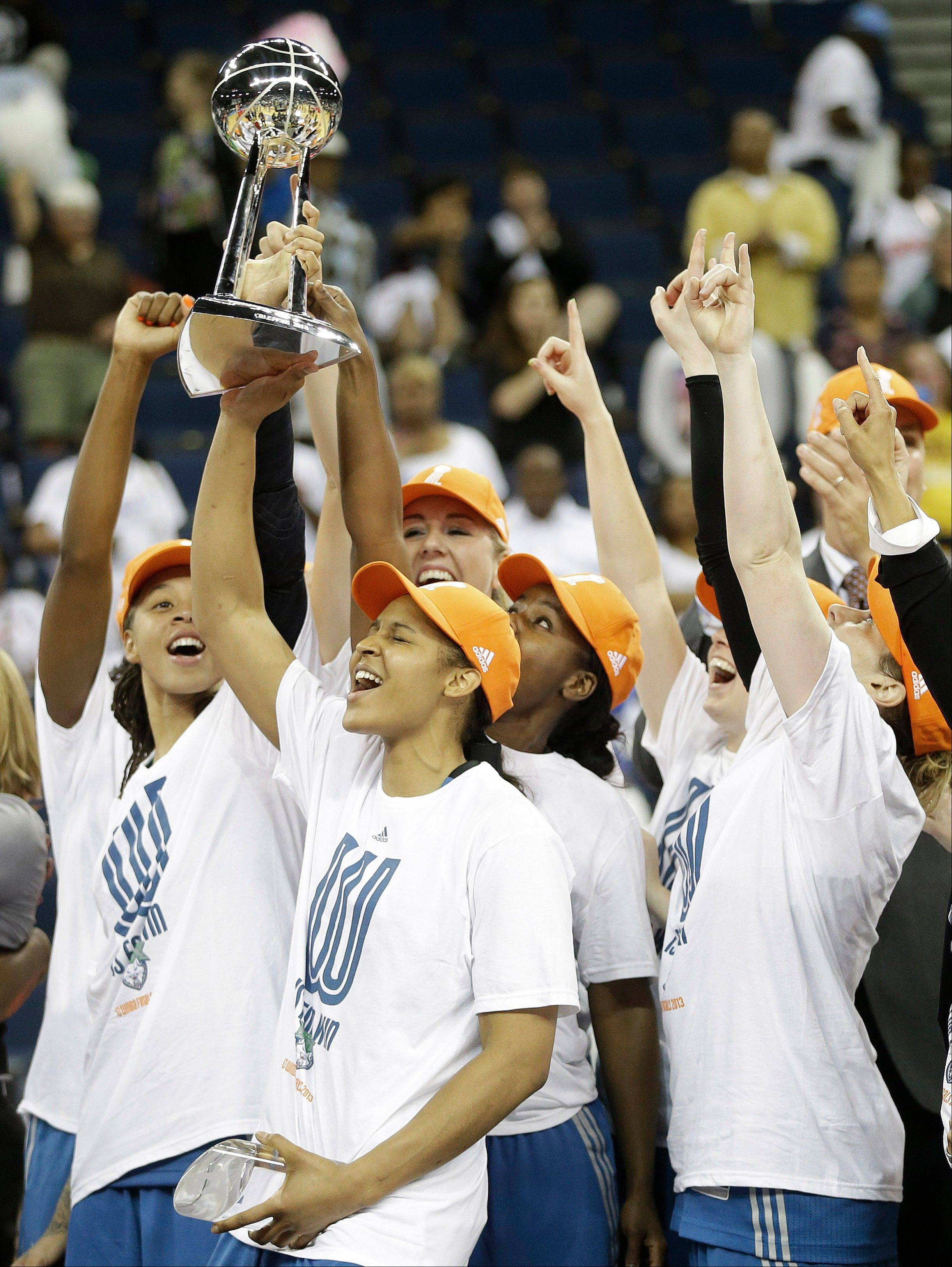 Minnesota Lynx' Maya Moore, second from left, holds the championship trophy with teammates after sweeping the Atlanta Dream in the WNBA Finals.