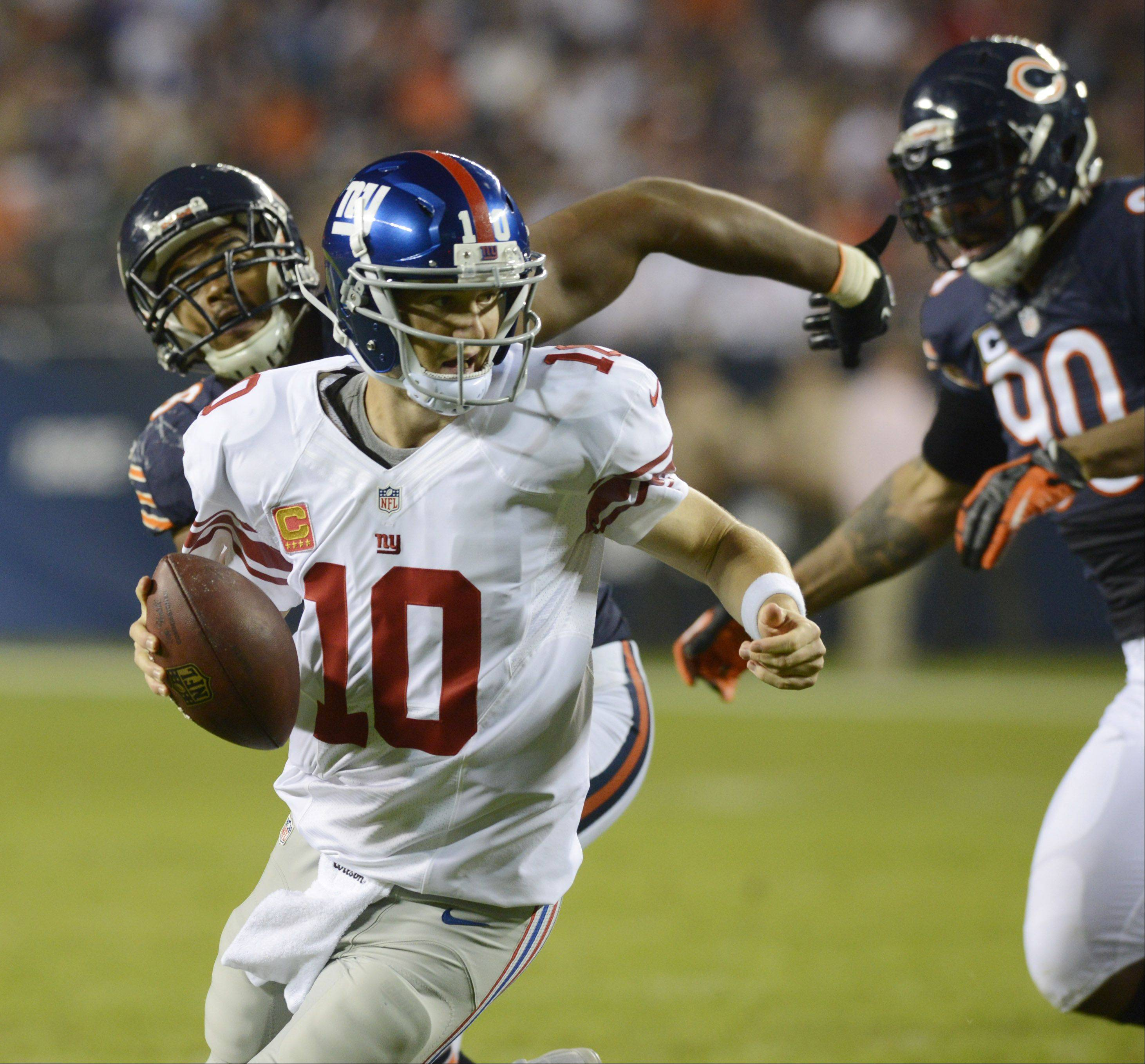 New York Giants quarterback Eli Manning eludes Chicago Bears defensive ends Corey Wootton, left, and Julius Peppers in Thursday's game. The Bears defense recorded only 1 sack.