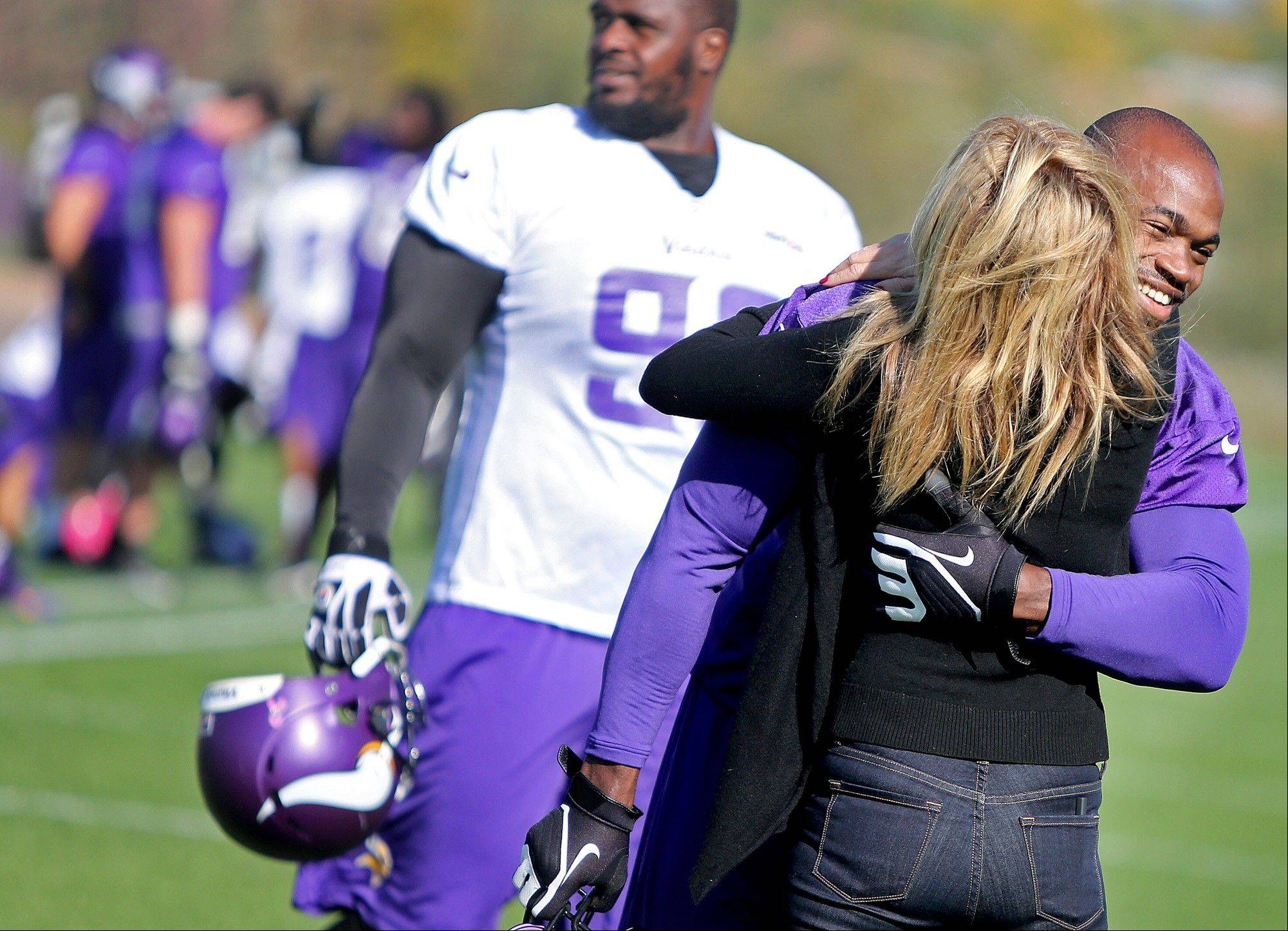 Minnesota Vikings' Adrian Peterson, right, receives a hug from an unidentified person during an NFL football practice field at Winter Park in Eden Prairie, Minn., Friday, Oct. 11, 2013. Peterson said he is certain he will play Sunday despite a serious personal matter that caused him to miss practice earlier this week. (AP Photo/The Star Tribune, Elizabeth Flores) ST. PAUL PIONEER PRESS OUT; SOFT OUT MINNEAPOLIS-AREA TV NOT TV OUT; MAGAZINES OUT