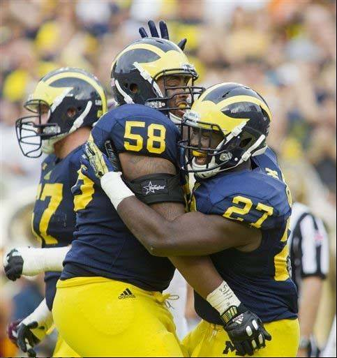 Michigan offensive lineman Chris Bryant (58) celebrates with running back Derrick Green (27) after a touchdown in the third quarter of last Saturday's win over Minnesota.
