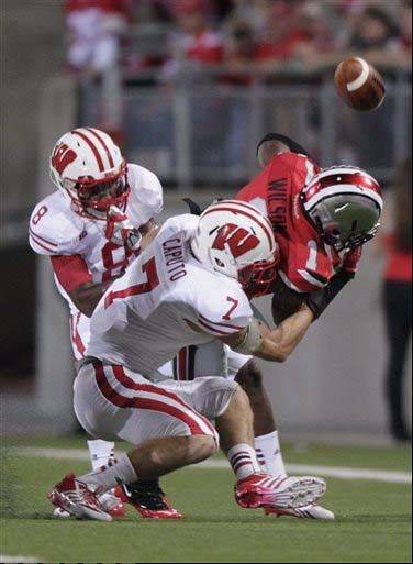 Wisconsin defenders Sojourn Shelton, left, and Michael Caputo, front, break up a pass intended for Ohio State running back Donte Wilson during the first quarter the Sept. 28 game in Columbus, Ohio.