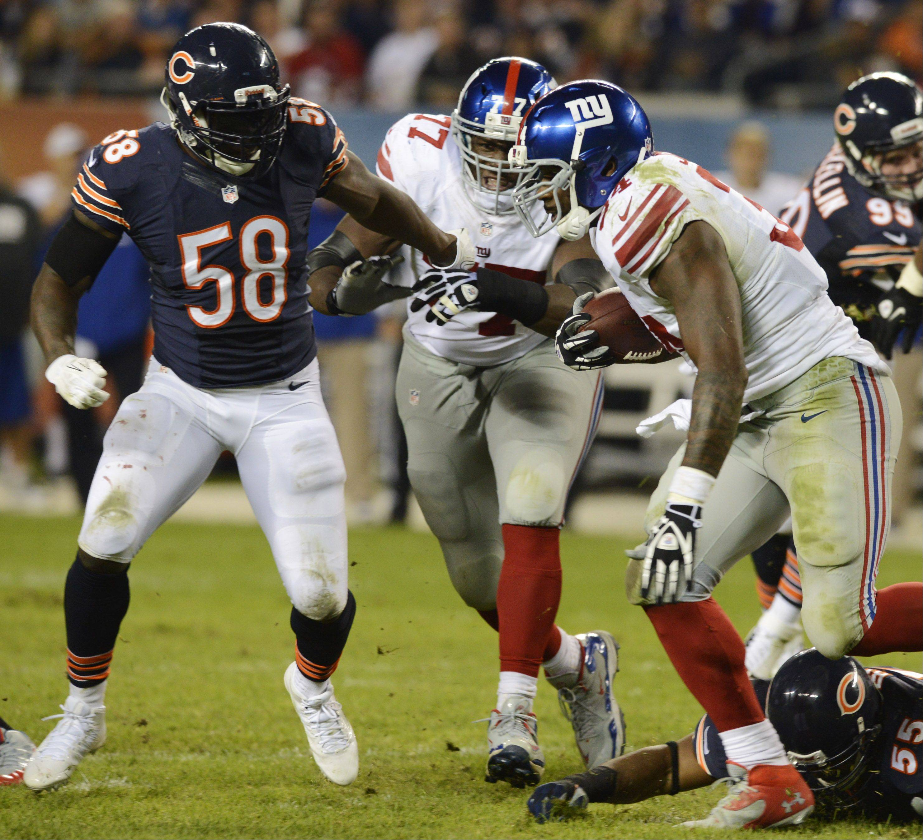 Bears middle linebacker D.J. Williams, here closing in on New York Giants running back Brandon Jacobs, was injured in during Thursday's game at Soldier Field and will be out for the season.