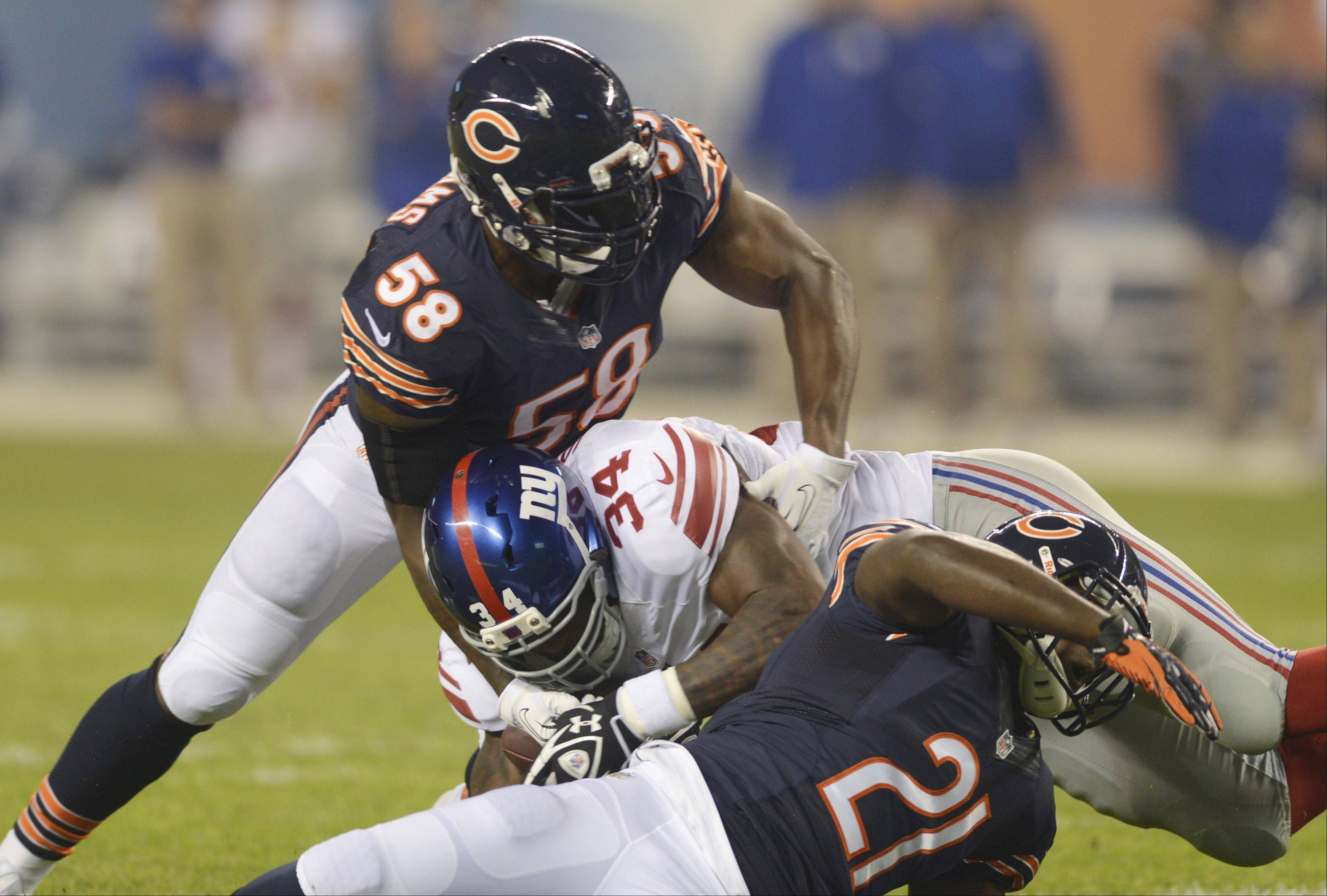 Middlelinebacker D.J. Williams (58) and safety Major Wright tackle Giants running back Brandon Jacobs Thursday night at Soldier Field in Chicago. Williams suffered a season-ending injury in the game.