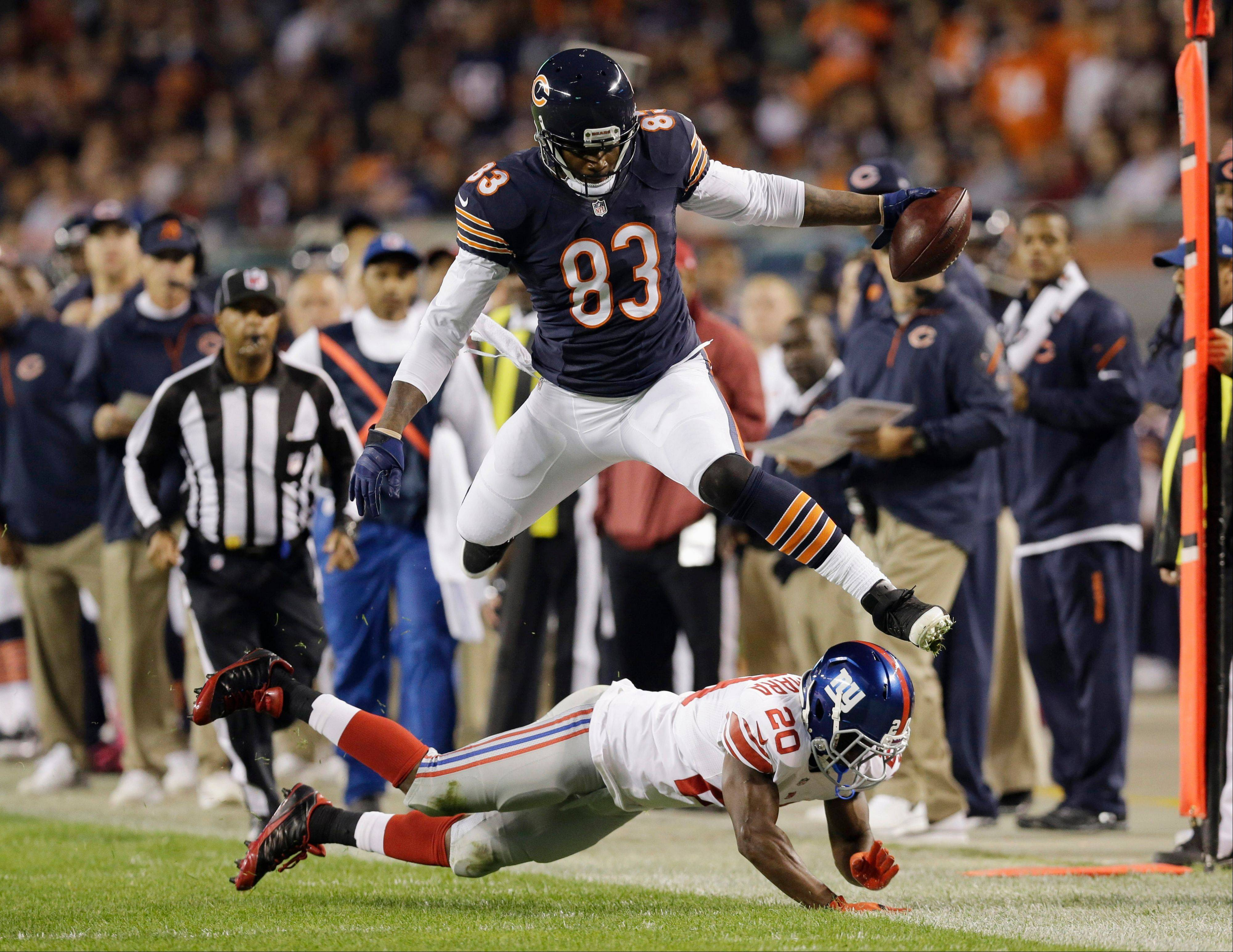 Chicago Bears tight end Martellus Bennett (83) leaps over New York Giants cornerback Prince Amukamara (20) in the first half of an NFL football game, Thursday, Oct. 10, 2013, in Chicago.