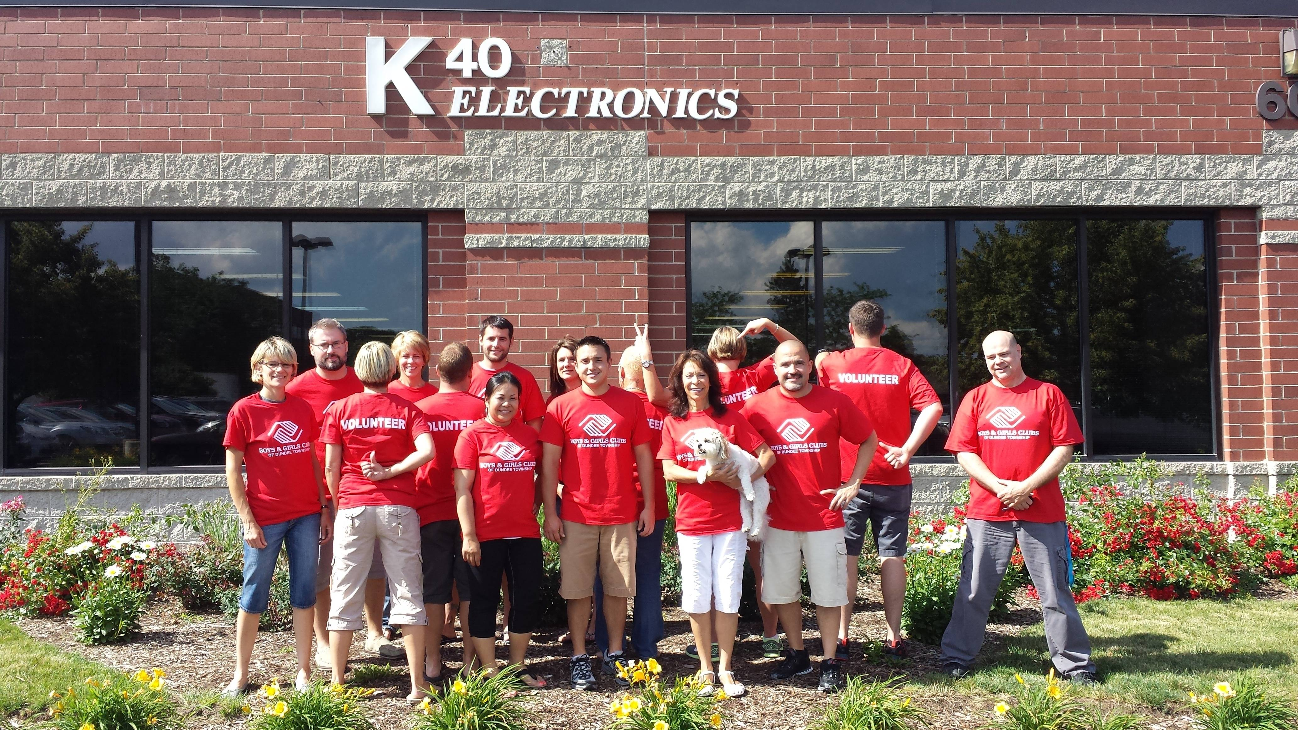 "The creative K40 Electronics team have some fun and ""ham it up"" outside their Elgin headquarters. Owner/President Peggy Finley is shown holding Sydney, the star of their must-see video."
