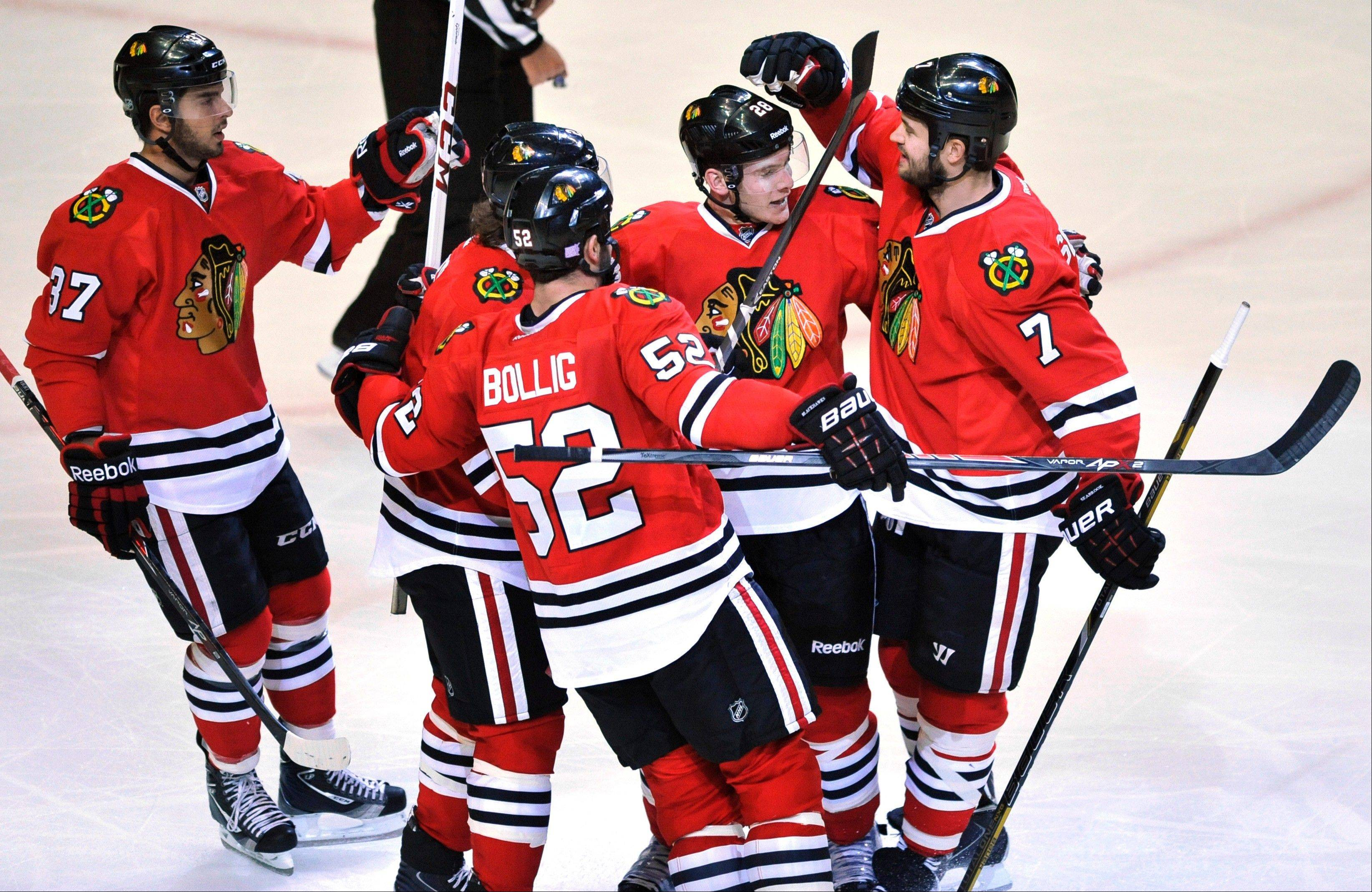 Blackhawks winger Ben Smith, second from right, celebrates his first-period goal Saturday with his teammates at United Center.