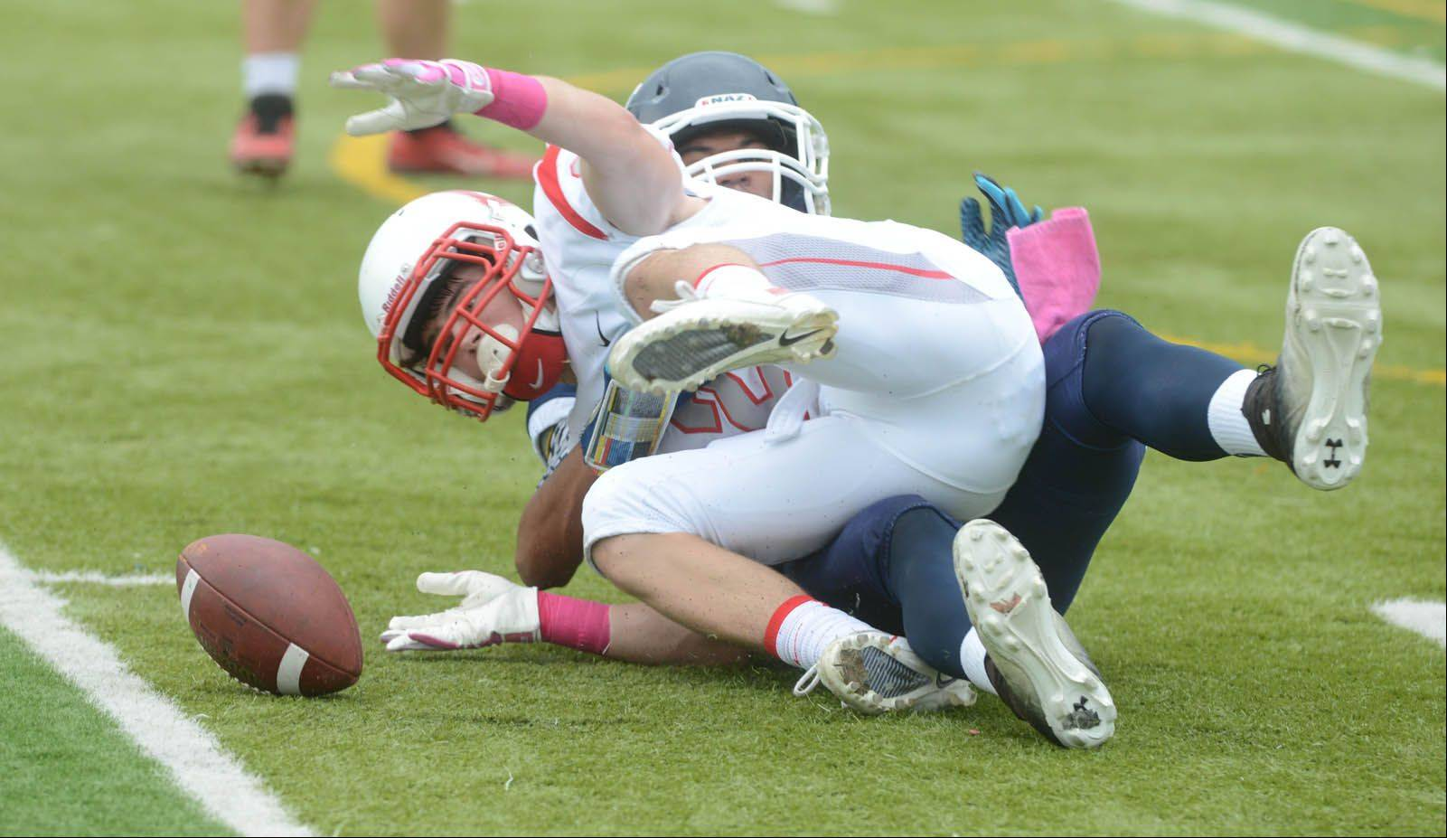 Brad Sznajder of Benet is pulled down by a defender during the Benet at Nazareth football game Saturday. He dropped the ball upon impact.