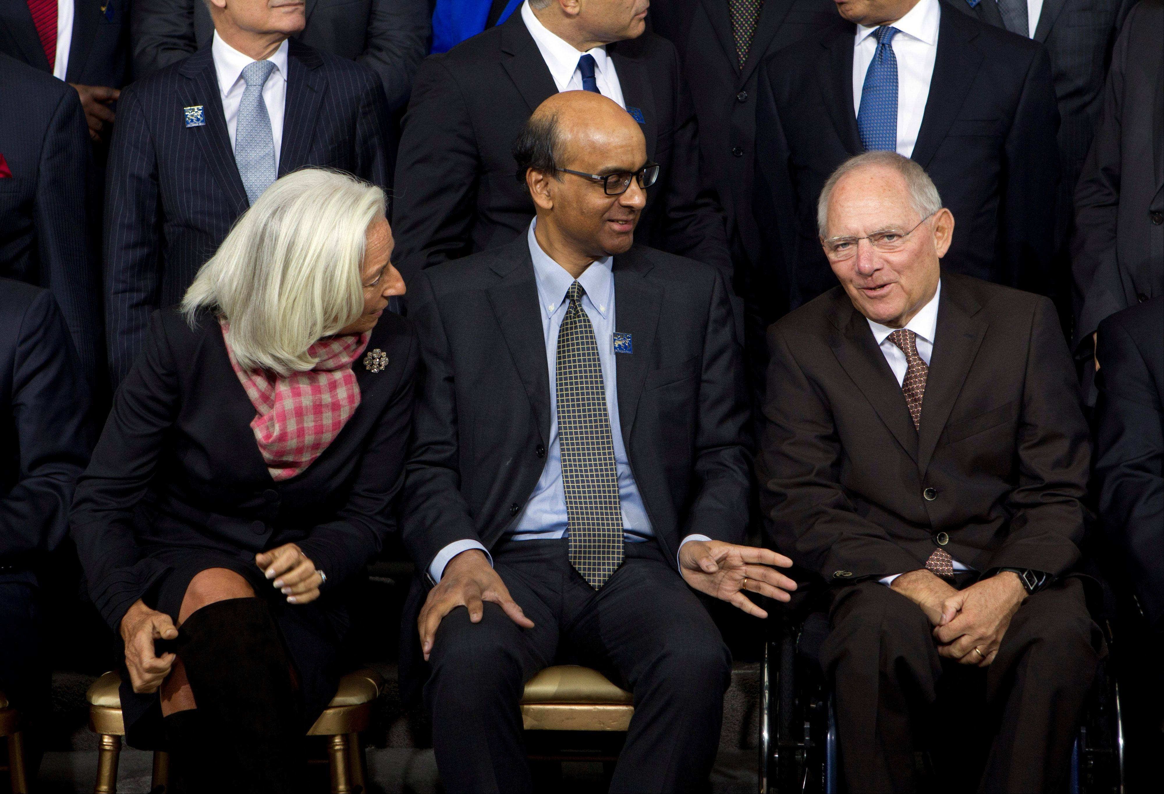 International Monetary Fund Managing Director Christine Lagarde, left, speaks with Singapore Finance Minister Tharman Shanmugaratnam and German Finance Minister Wolfgang Schaeuble, right, during a group photo Saturday at IMF headquarters in Washington.