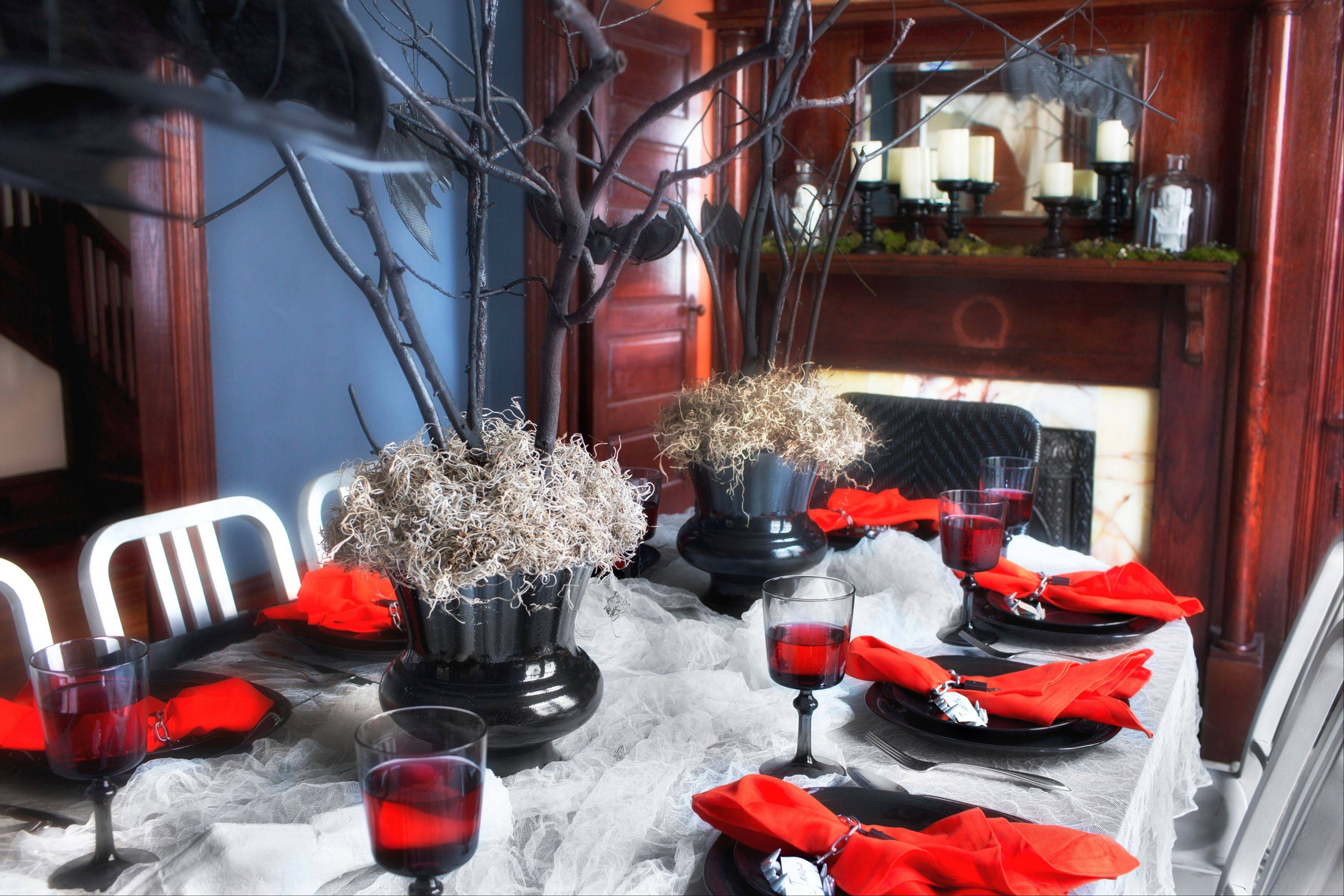Bare branches, spray-painted black and secured in vases with gravel, floral foam and a layer of moss, makes a stunning and inexpensive Halloween centerpiece perfect for an adult Halloween party.