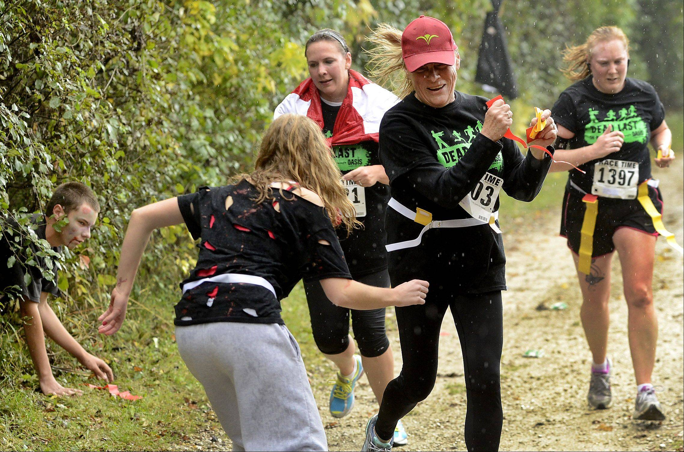 Zombie Cannon Hanebuth, a senior at Grayslake North High School, center, torments runners Saturday along the route during Grayslake's inaugural zombie run.