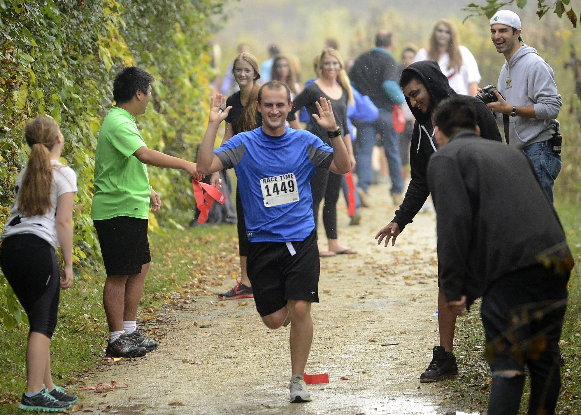 Grayslake North High School history teacher Robert Nicoletti runs the gauntlet of zombies Saturday during Grayslake's inaugural zombie run.