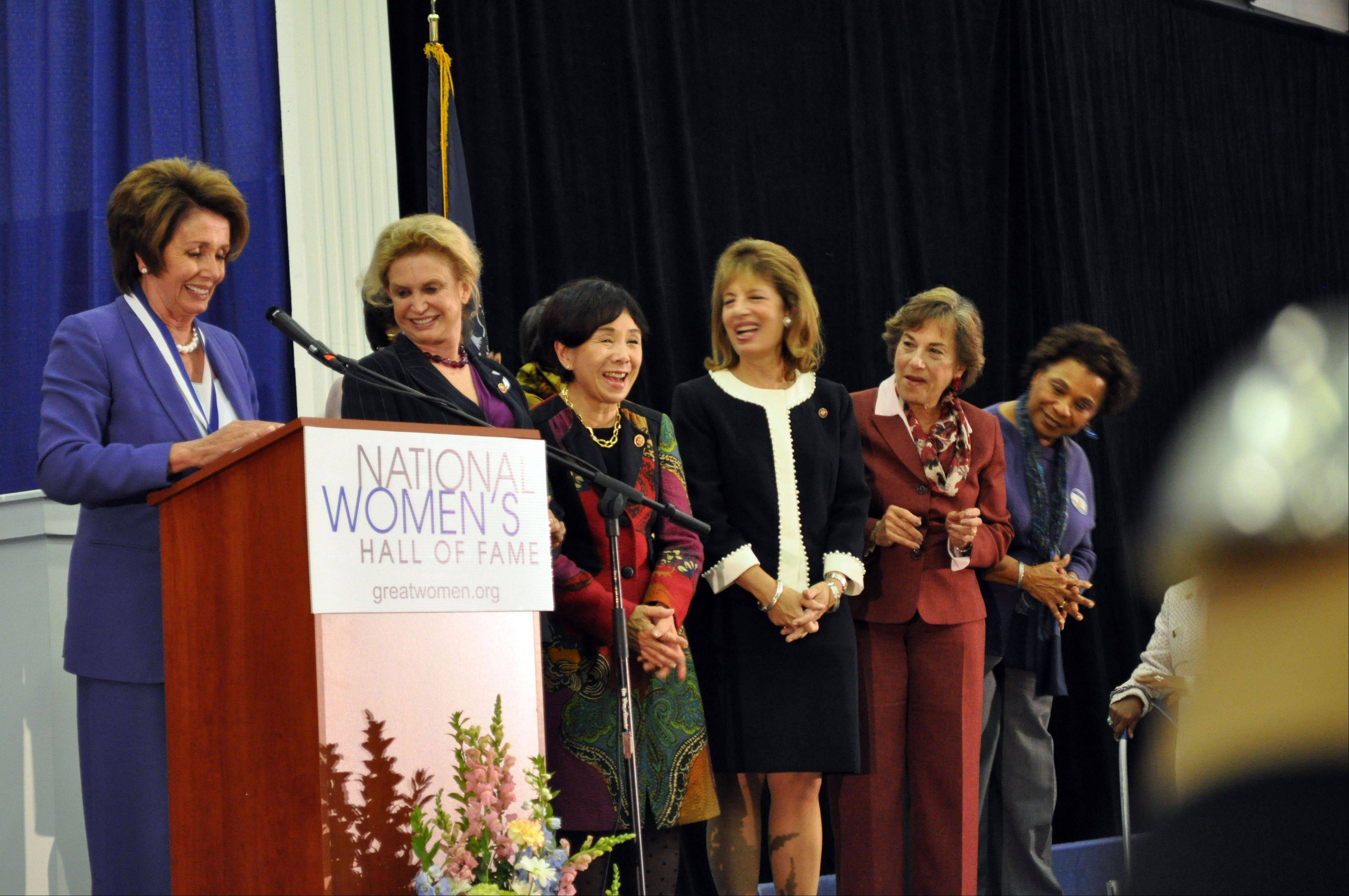 Nancy Pelosi invites fellow congresswomen onto the stage Saturday during her acceptance speech during the induction ceremony for the National Women's Hall of Fame at the New York Chiropractic College Athletic Center in Seneca Falls, N.Y.