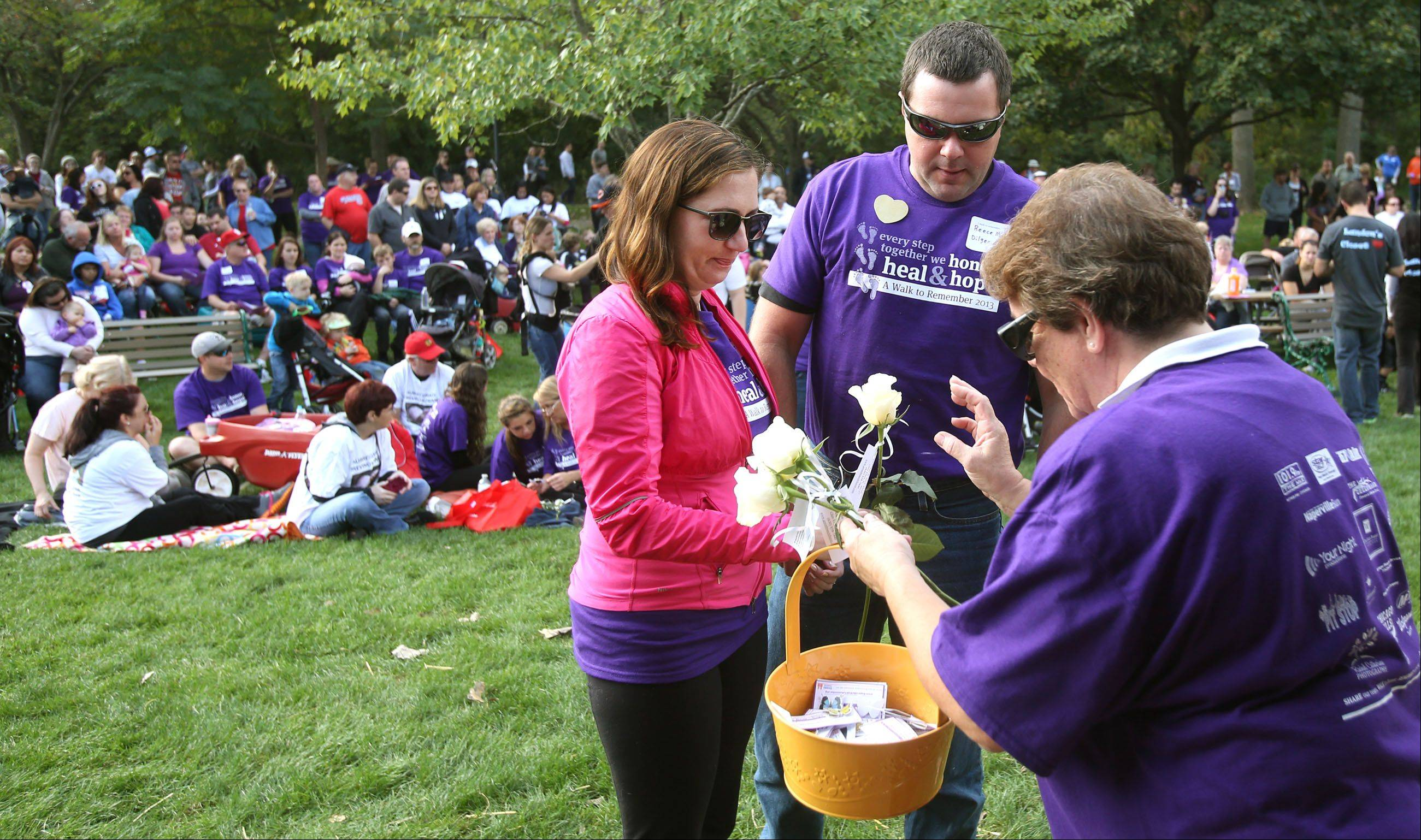 Brian and Katie Dilger of Naperville receive a rose from Kathy McNulty in honor of Reece Michael Dilger during Naperville's ninth annual A Walk to Remember. The walk benefits the Edward Foundation SHARE program.