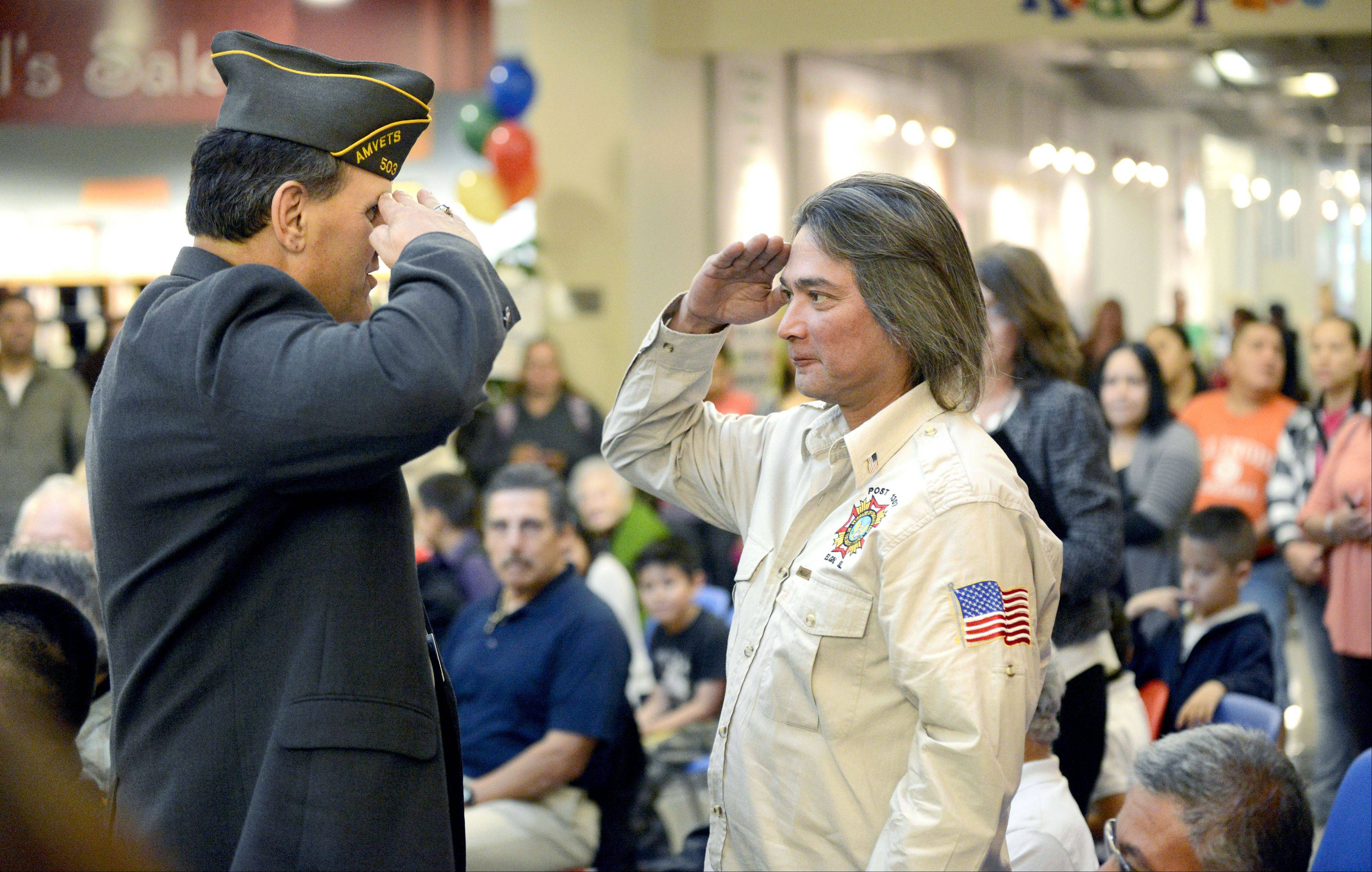 Army veteran Andrew Balafas, left, salutes Navy veteran Rupert Siete of Elgin after presenting him with a certificate of appreciation for his military service and giving him an American flag pin at the veterans ceremony kicking off the Hispanic Heritage Month Celebration at Gail Borden Public Library in Elgin.