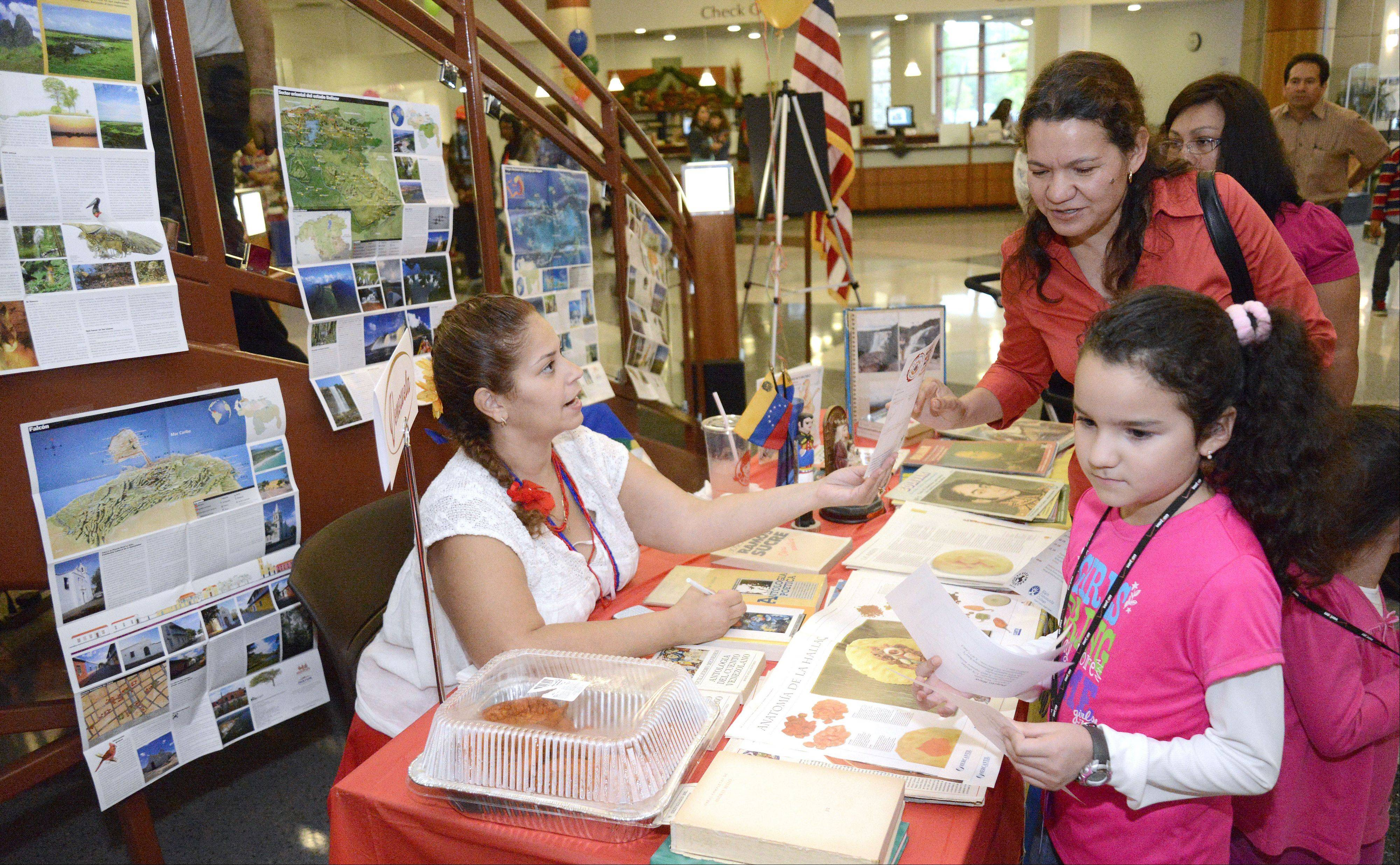 Navi Gonzalez of Elgin, left, talks to about her Venezuelan heritage to Gloria Melchor and her daughter, Litzy, 8, also of Elgin, at the Hispanic Heritage Month Celebration at Gail Borden Public Library in Elgin on Saturday.