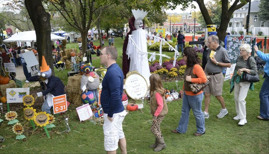 Visitors take in the sights, voting for their favorite entries at the Scarecrow Fest in St. Charles' Lincoln Park on Saturday.