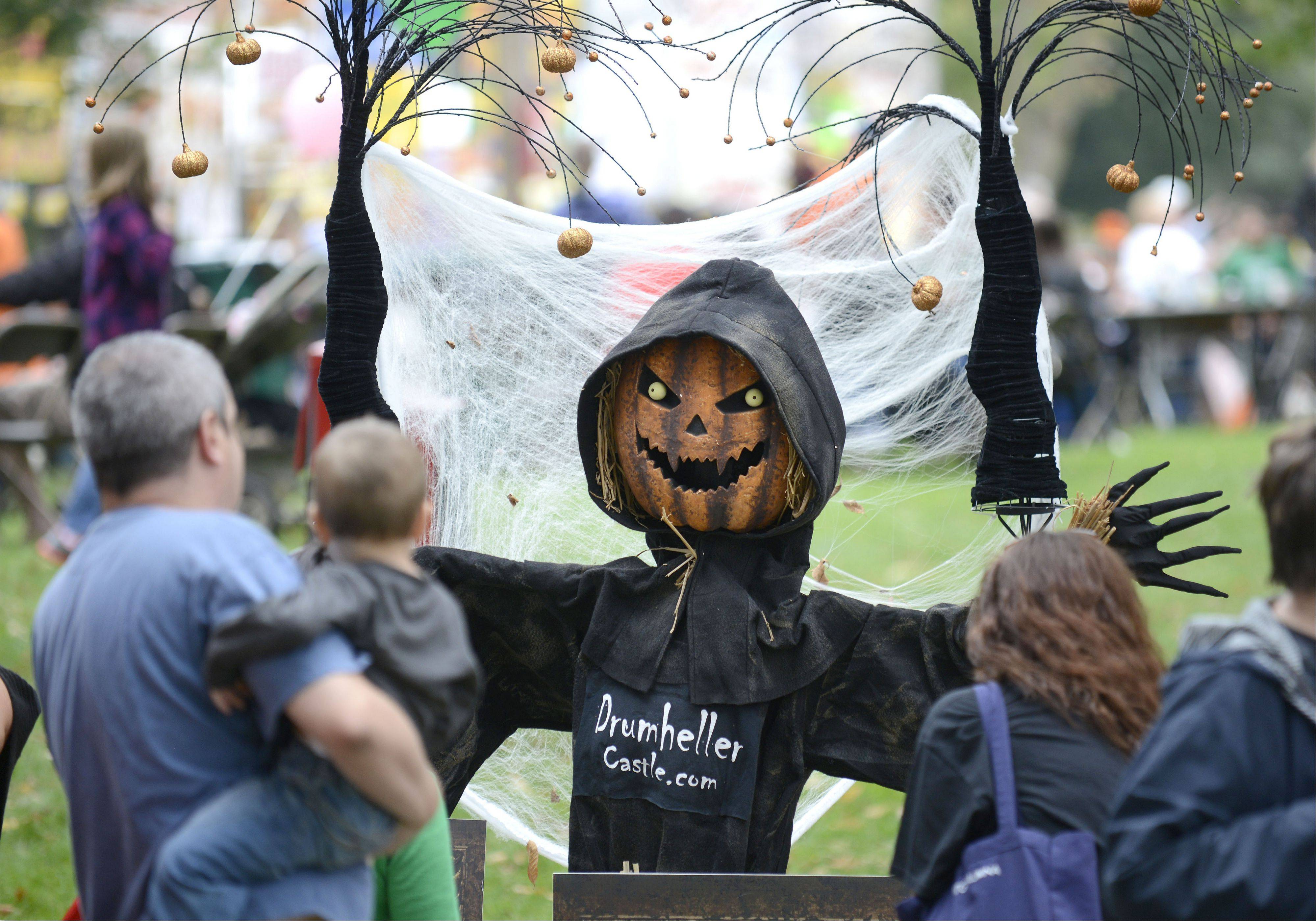 "Visitors vote for their favorite entries at the Scarecrow Fest in St. Charles' Lincoln Park on Saturday. This entry is based on the book ""Haunted Nights at Drumheller Castle: A St. Charles Tall Tale"" by local author Faly Burmeister."