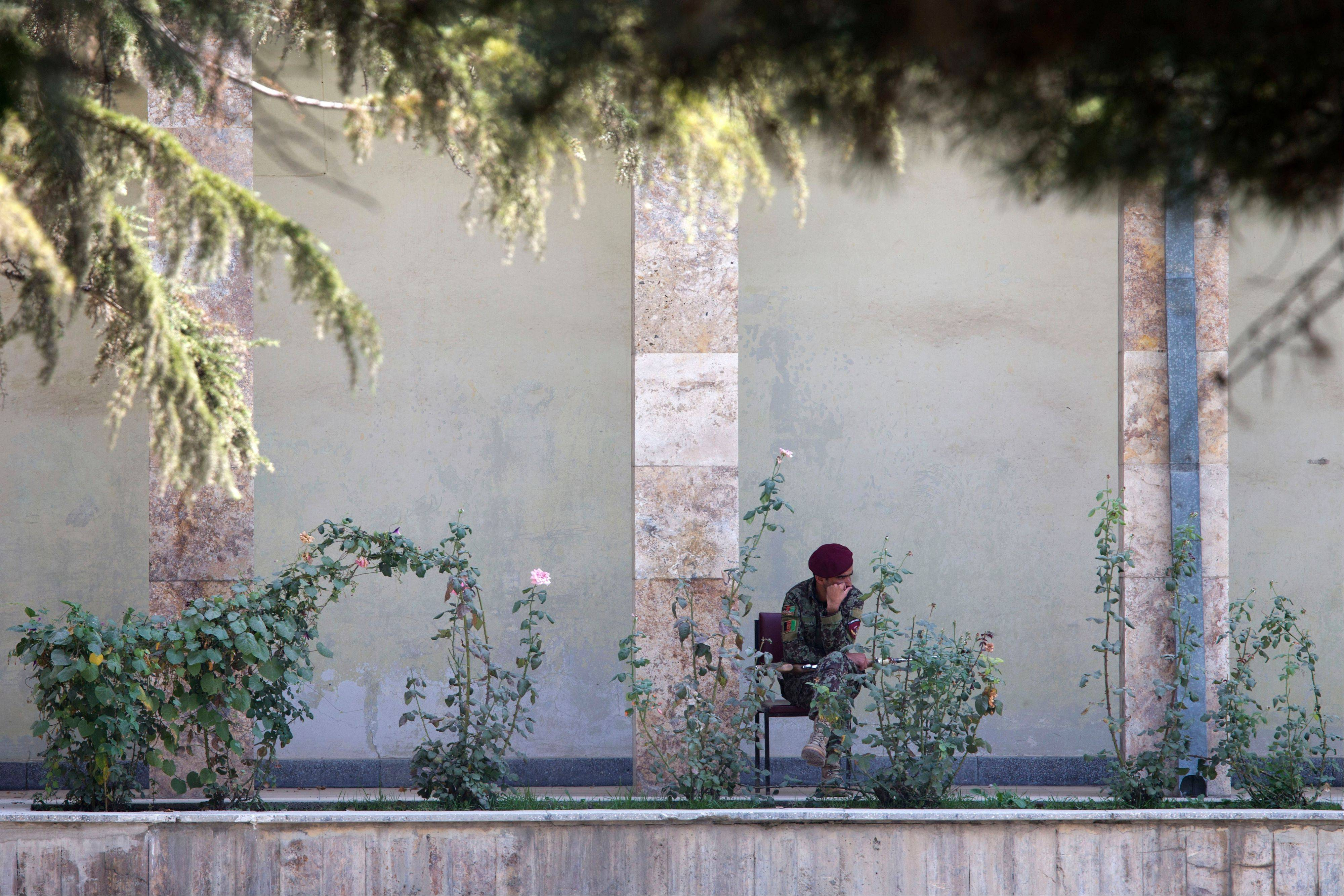 An Afghan soldier rests as a news conference is delayed Saturday between U.S. Secretary of State John Kerry and Afghan President Hamid Karzai at the presidential palace in Kabul, Afghanistan.