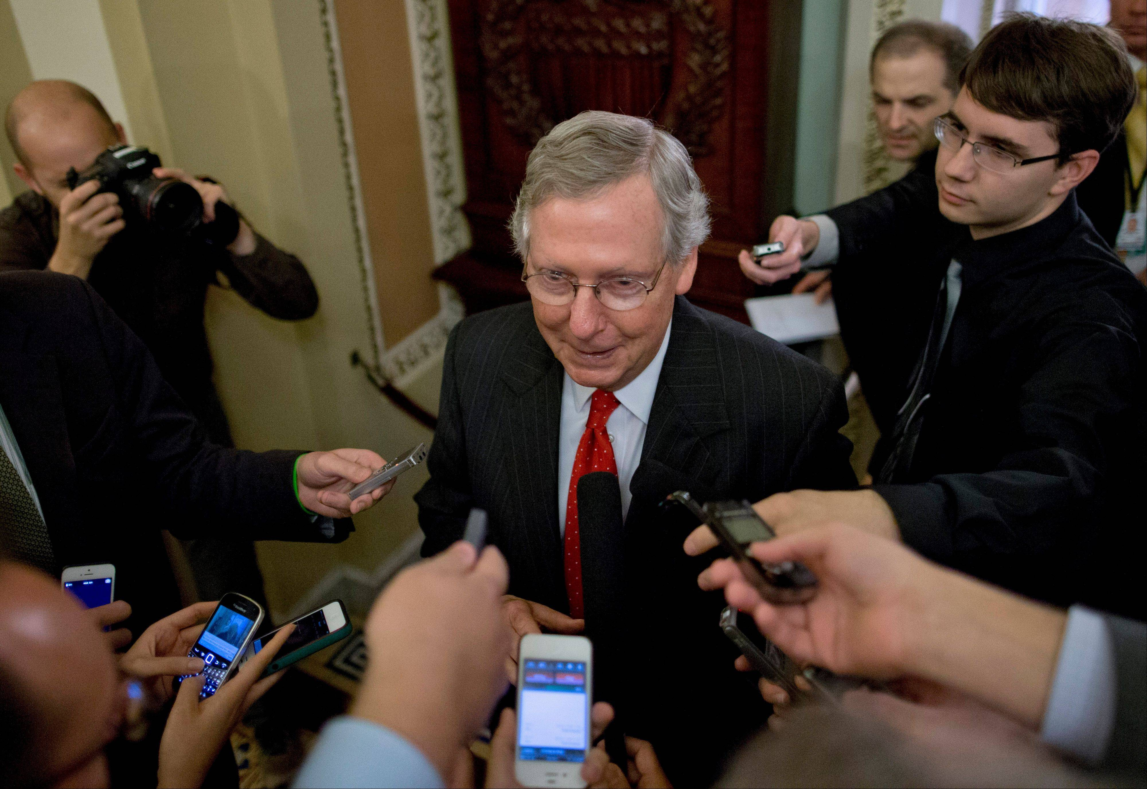 Senate Minority Leader Rep. Mitch McConnell of Kentucky speaks with reporters after returning Friday to Capitol Hill in Washington.