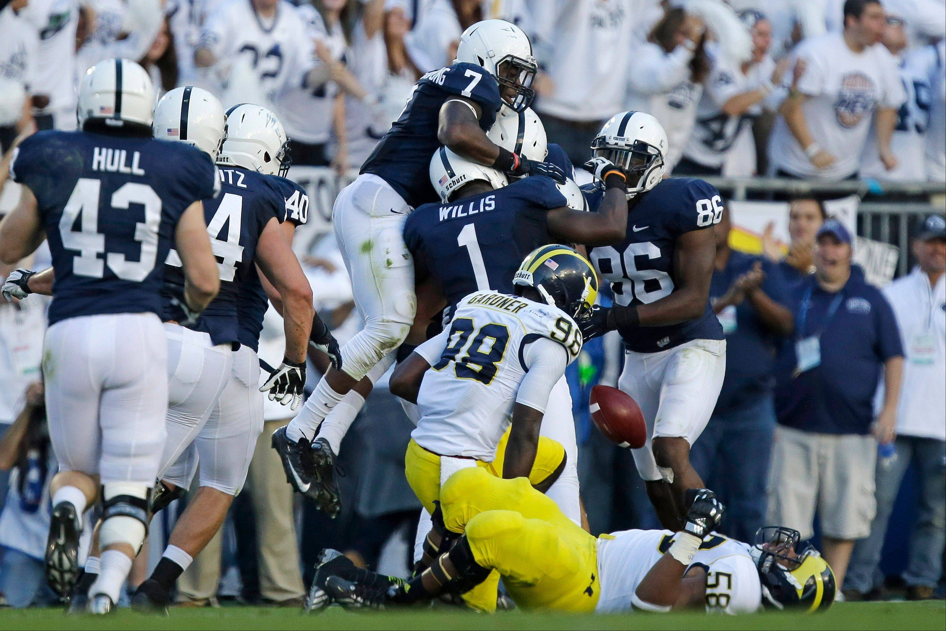 The Penn State defense celebrates an interception by Penn State defensive end Anthony Zettel (98) behind Michigan quarterback Devin Gardner (98) and Michigan offensive linesman Chris Bryant (58) during the second quarter of an NCAA college football game in State College, Pa., Saturday, Oct. 12, 2013.