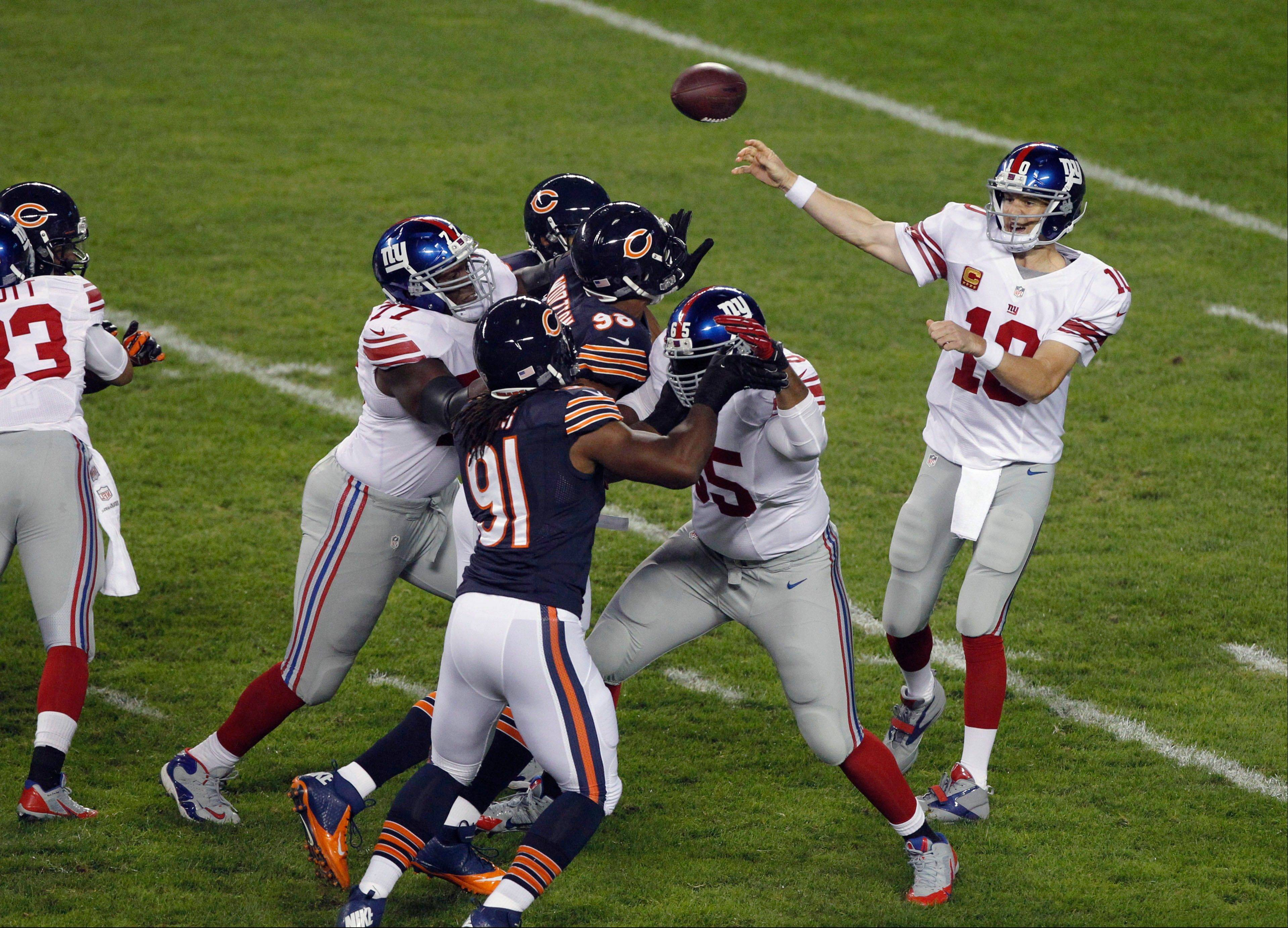 New York Giants quarterback Eli Manning (10) throws a pass which was intercepted by Chicago Bears defensive back Zack Bowman in the first half of an NFL football game, Thursday, Oct. 10, 2013, in Chicago.
