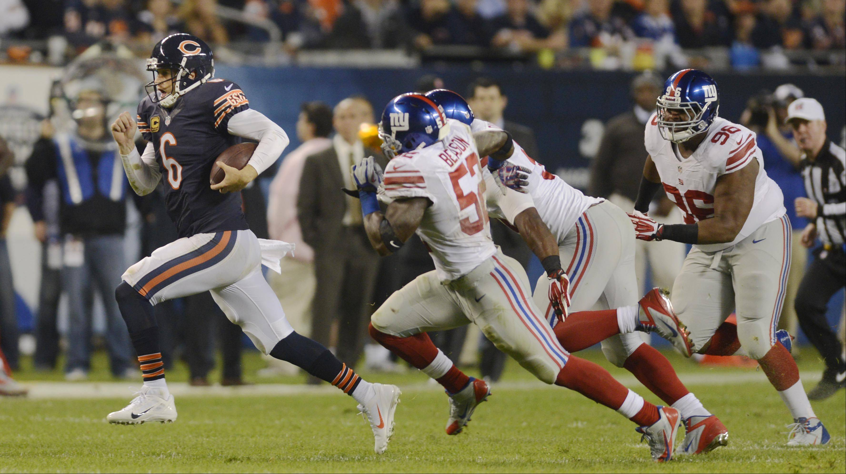 Bears quarterback Jay Cutler is chased to the sidelines by the New York Giants Thursday night at Soldier Field in Chicago.