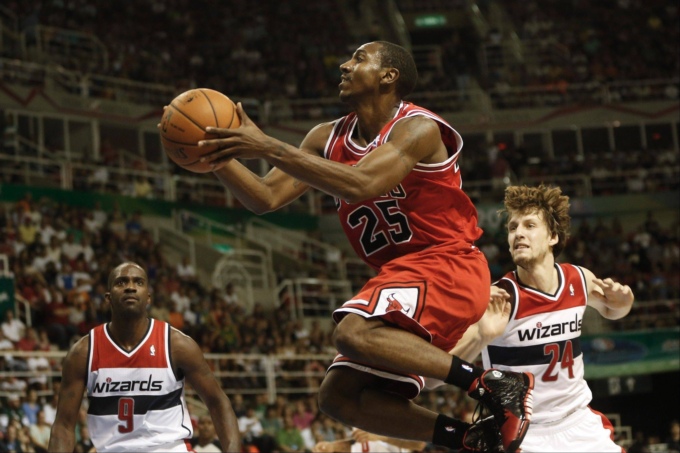 The Bulls' Marquis Teague, center, makes a move to the basket as Washington Wizards' Martell Webster, left, and Jan Vesely look on during the first half of an NBA preseason basketball game in Rio de Janeiro, Brazil, Saturday.
