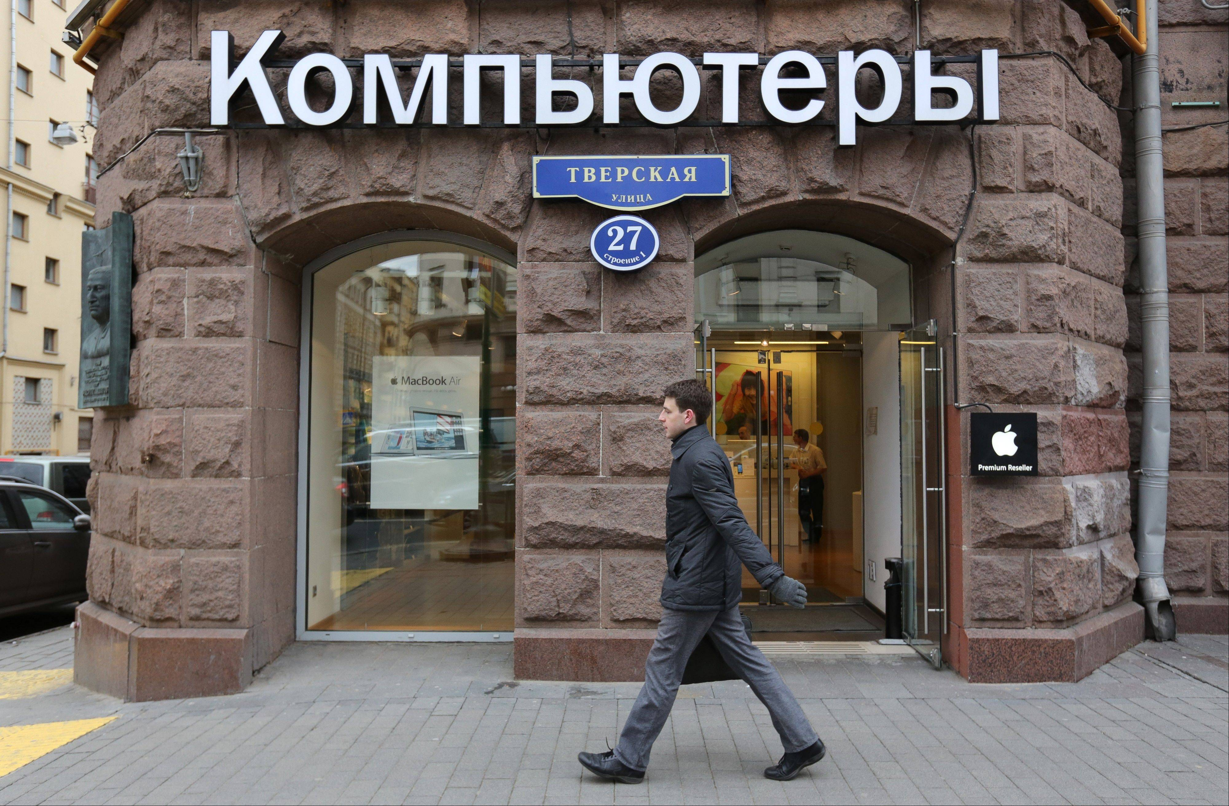 A pedestrian passes the entrance to a re:Store premium Apple Inc. reseller in Moscow.