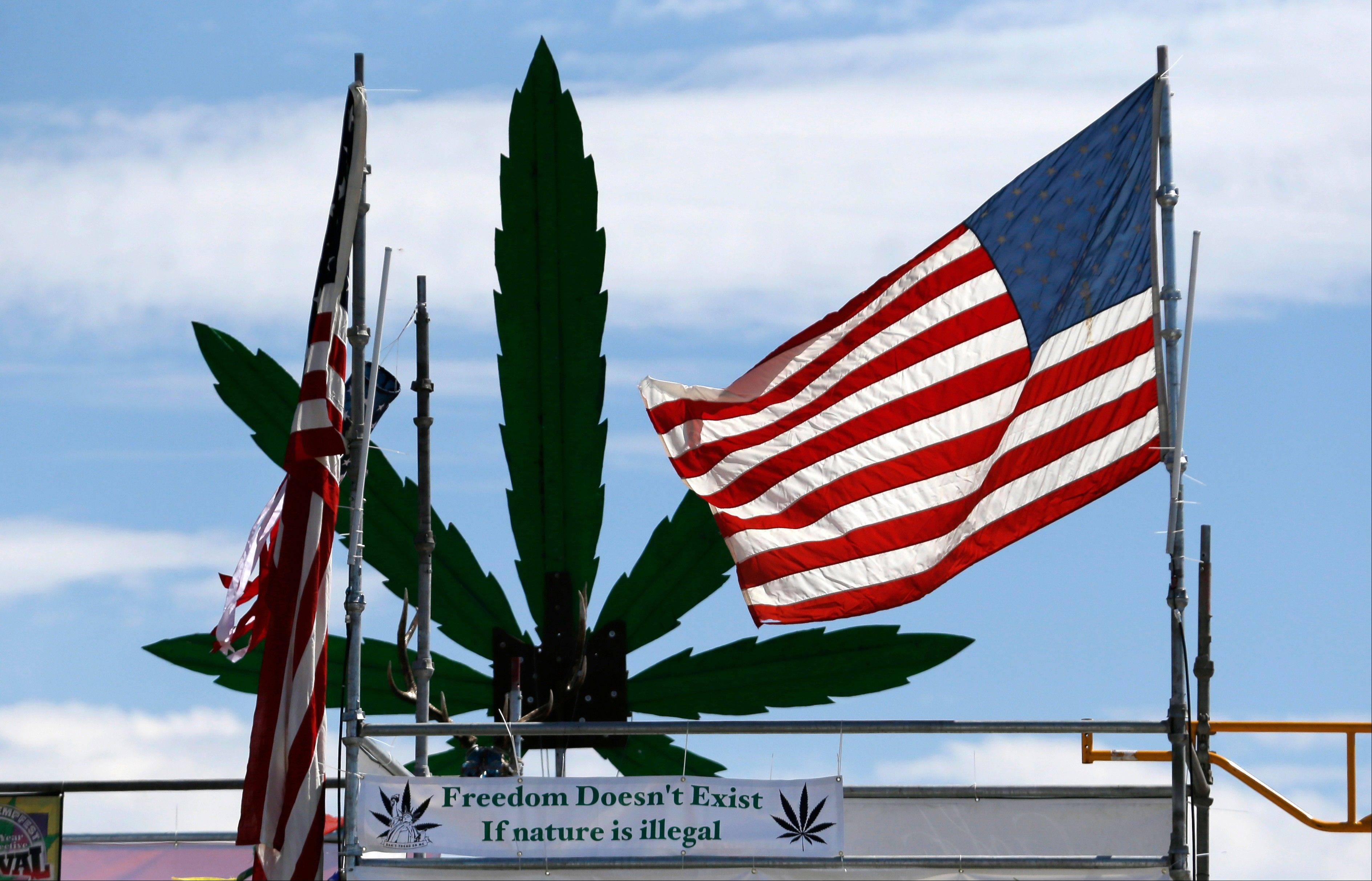An American flag flies atop the stage at the first day of Hempfest on Aug. 16 in Seattle. Thousands packed the Seattle waterfront park for the opening of a three-day marijuana festival � an event that is part party, part protest and part victory celebration after the legalization of pot in Washington and Colorado last fall.