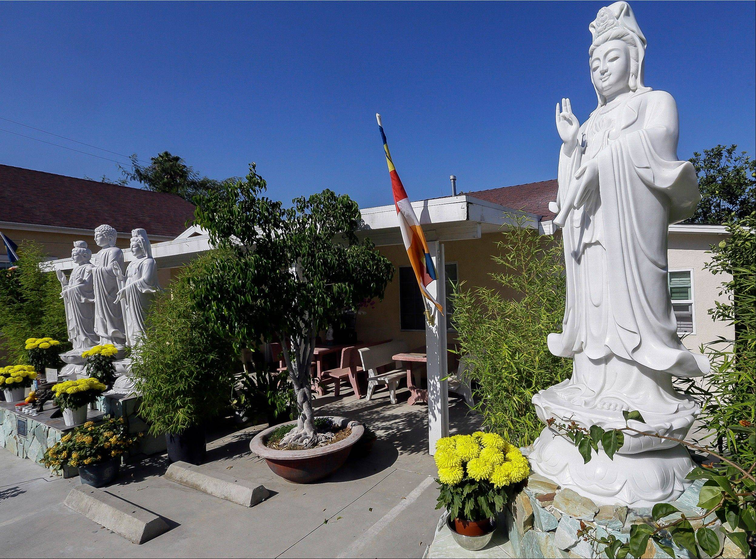 In this Sept. 18, 2013, photo, Buddhist statues decorate the entrance to the Lu Mountain Temple in Rosemead, Calif. The temple has become a repository for the colorful crystals and a tooth and a hair that are believed to have come from the body of the Buddha himself.