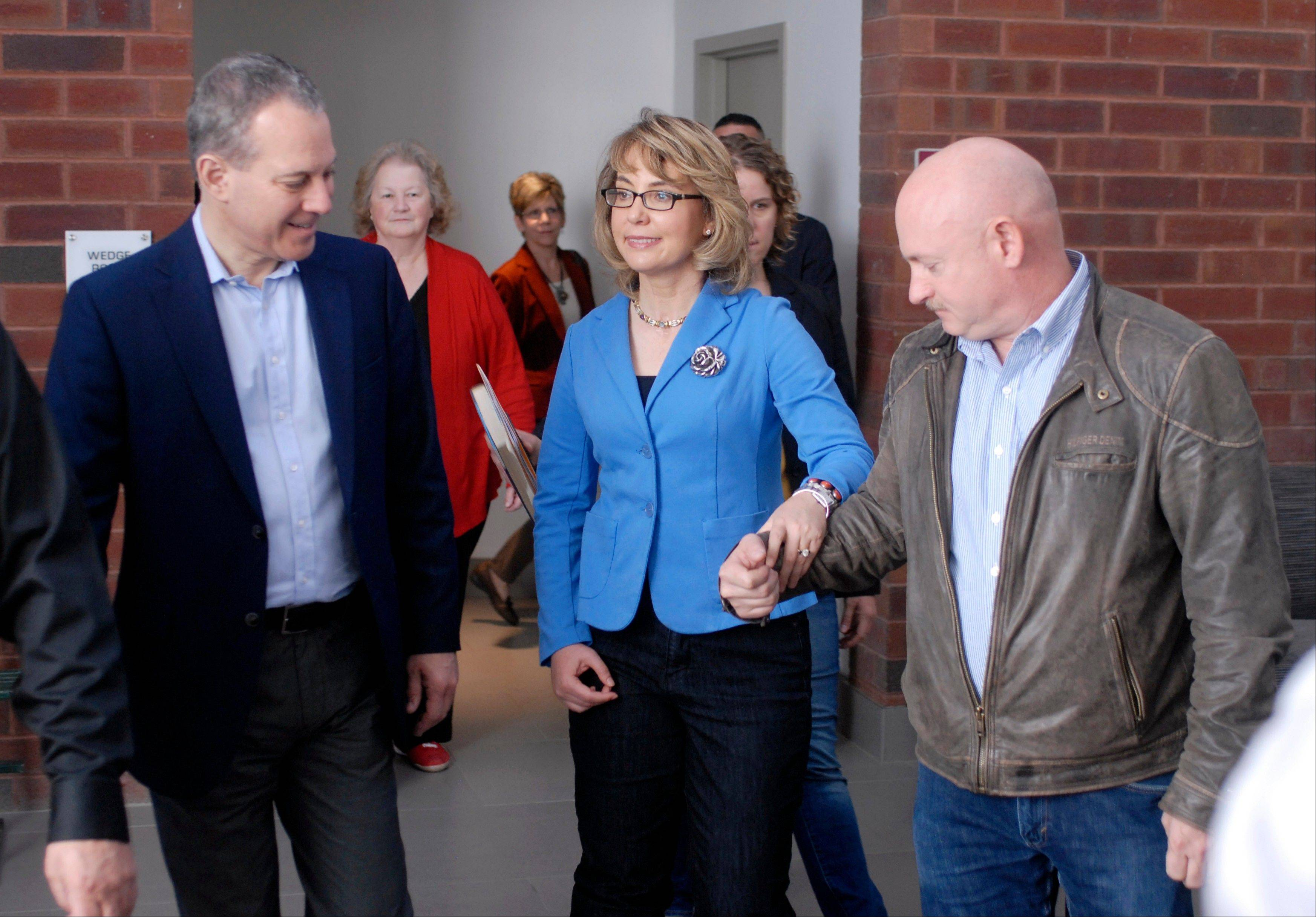 New York Attorney General Eric Schneiderman, left, former U.S. Rep Gabrielle Giffords, center, and her husband, Mark Kelly, arrive for a tour of the New EastCoast Arms Collectors Associates arms fair in Saratoga Springs, N.Y. on Sunday.