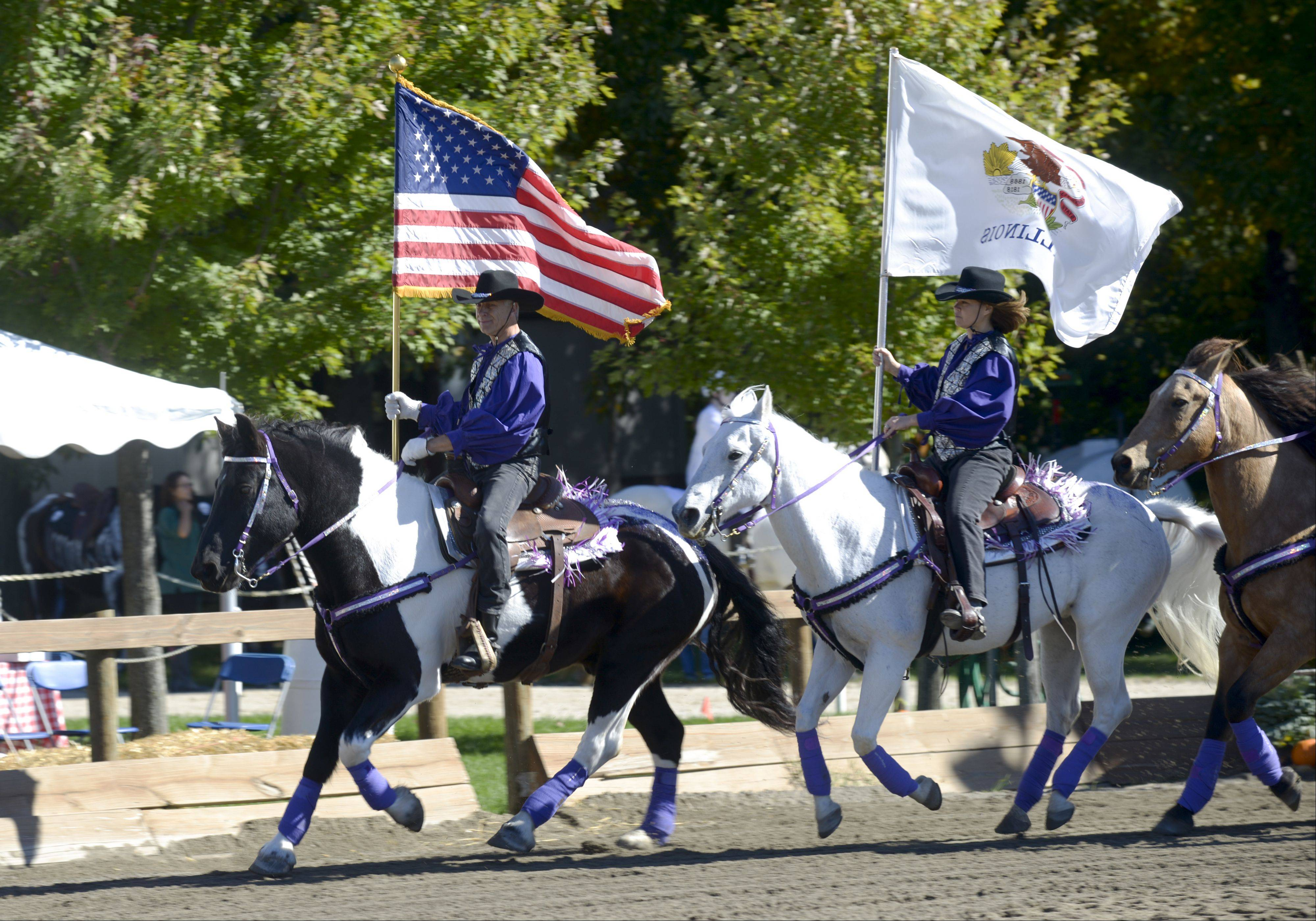 Rick Vlahos of the MidWest Renegade Equestrian Drill Team leads the team during the singing of the national anthem to kick off the Danada Fall Festival on Sunday in Wheaton.