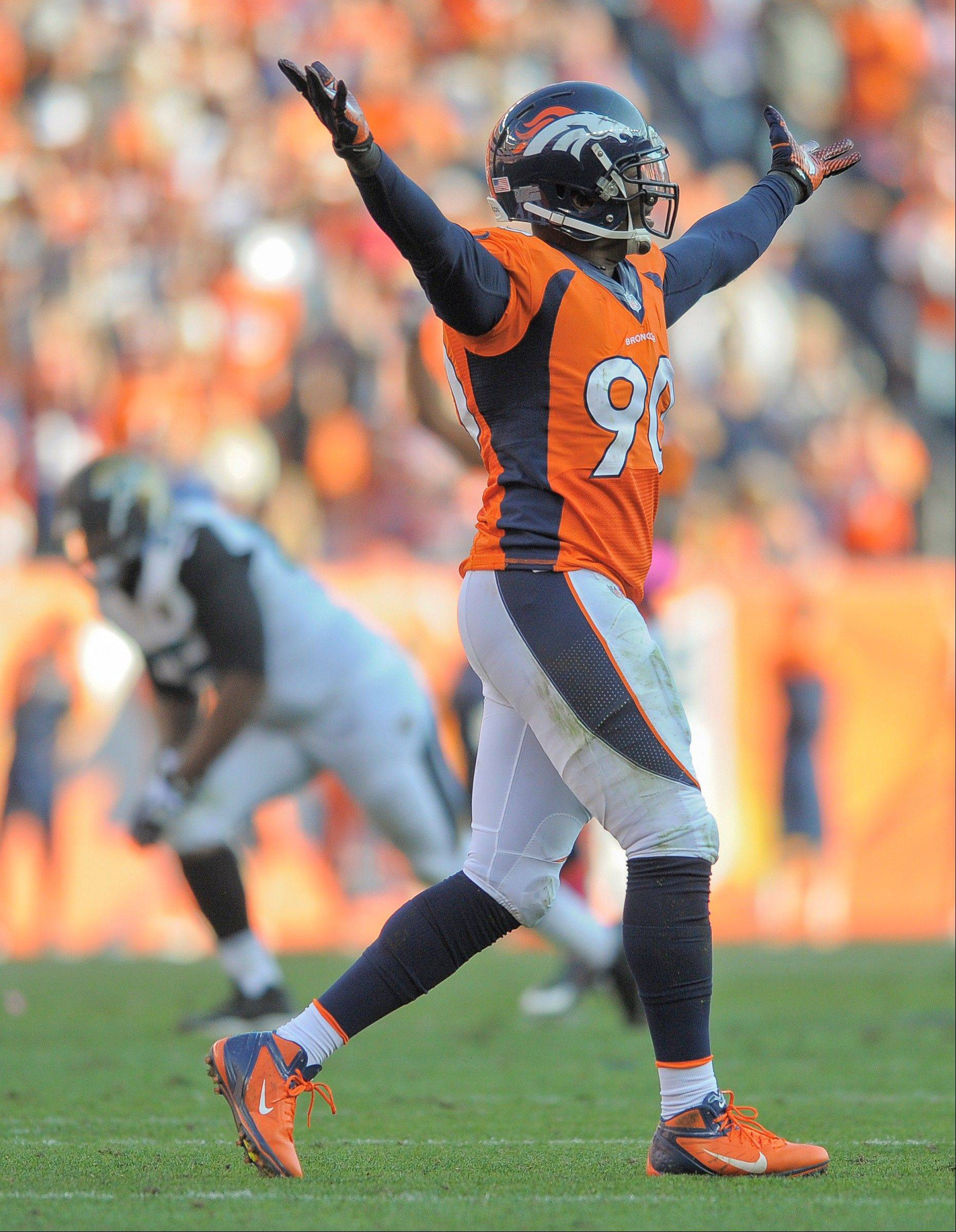 Denver Broncos defensive end Shaun Phillips (90) raises up his arms after a defensive play against the Jacksonville Jaguars in the fourth quarter of an NFL football game, Sunday, Oct. 13, 2013, in Denver.