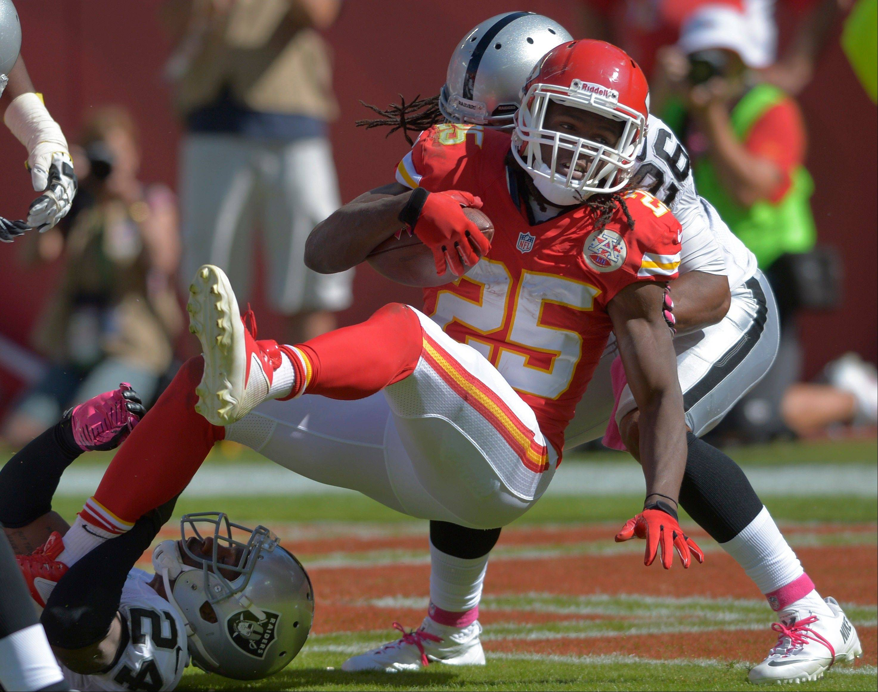 Chiefs running back Jamaal Charles crosses the goal line for a touchdown as Oakland free safety Usama Young defends during the first half of Sunday�s game in Kansas City, Mo.