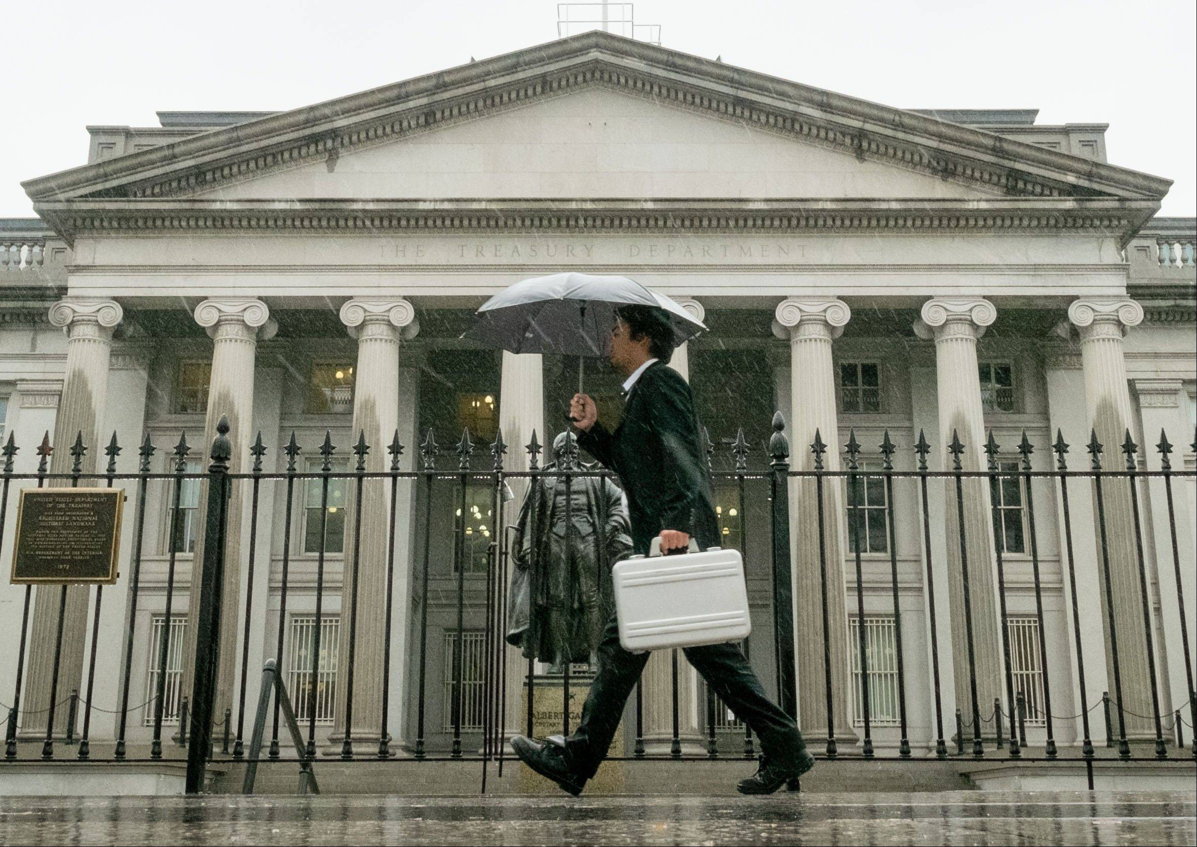 In this TOct. 10 photo, a pedestrian walks past the U.S. Treasury Building in Washington on a rainy day. The national debt actually reached the limit in May 2013. Since then, Treasury Secretary Jacob Lew has made accounting moves to continue financing the government without further borrowing. But Lew says those measures will be exhausted by Thursday, Oct. 17. The government will then have to pay its bills from its cash on hand an estimated $30 billion and tax revenue.