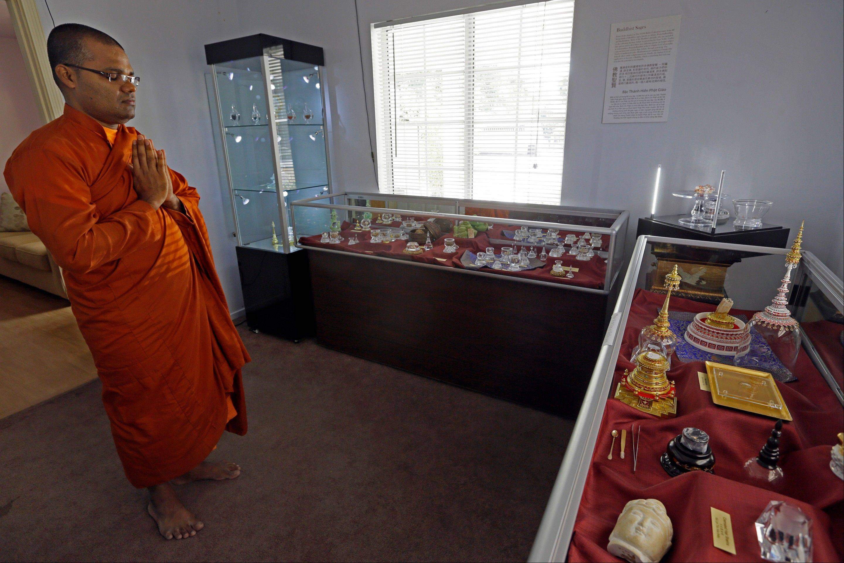 In this Sept. 18, 2013, photo, Bhante Wanarathana prays in a room displaying Buddhist relics at the Lu Mountain Temple in Rosemead, Calif. The temple has become a repository for the colorful crystals and a tooth and a hair that are believed to have come from the body of the Buddha himself.