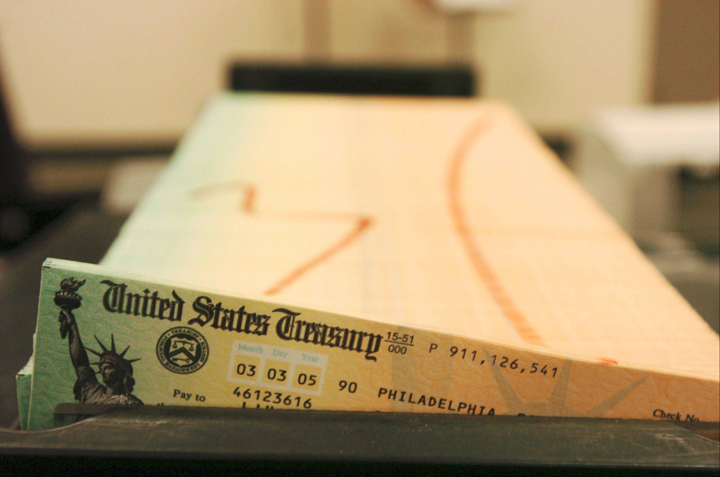 In this Feb. 11, 2005 file photo, trays of printed Social Security checks wait to be mailed from the U.S. Treasury's Financial Management services facility in Philadelphia. For the second straight year, millions of Social Security recipients can expect an historically small increase in benefits come January 2014.