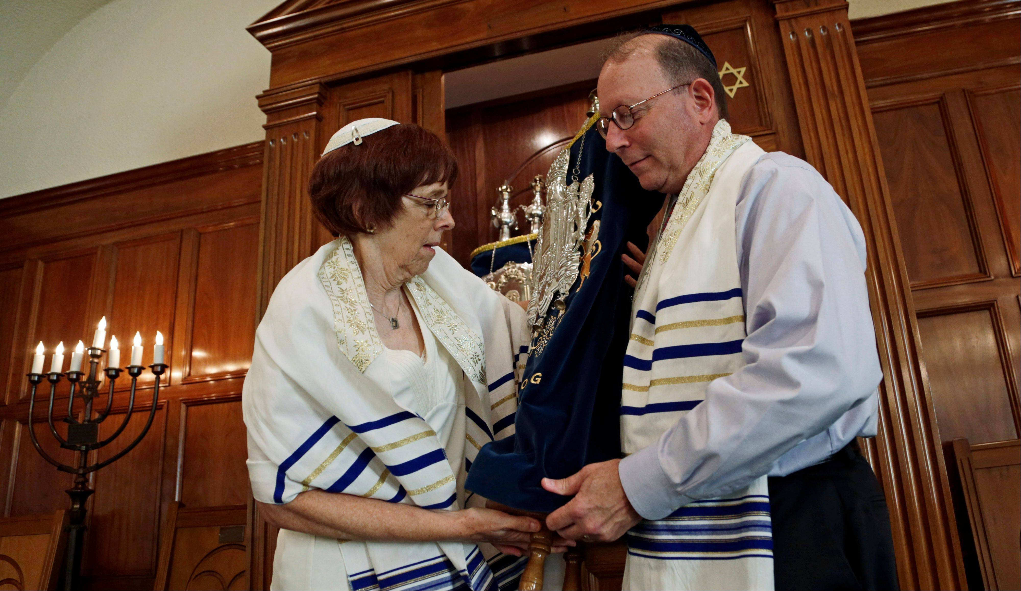 In this Oct. 2, 2013 photo, Rabbi Lynne Goldsmith and her husband Rob Goldsmith remove the Torah from the Ark inside Temple Emanu-El in Dothan, Ala. Faced with a dwindling, aging congregation, members of a south Alabama synagogue five years ago began recruiting Jews to move to Dothan with the promise of $50,000 in relocation assistance.