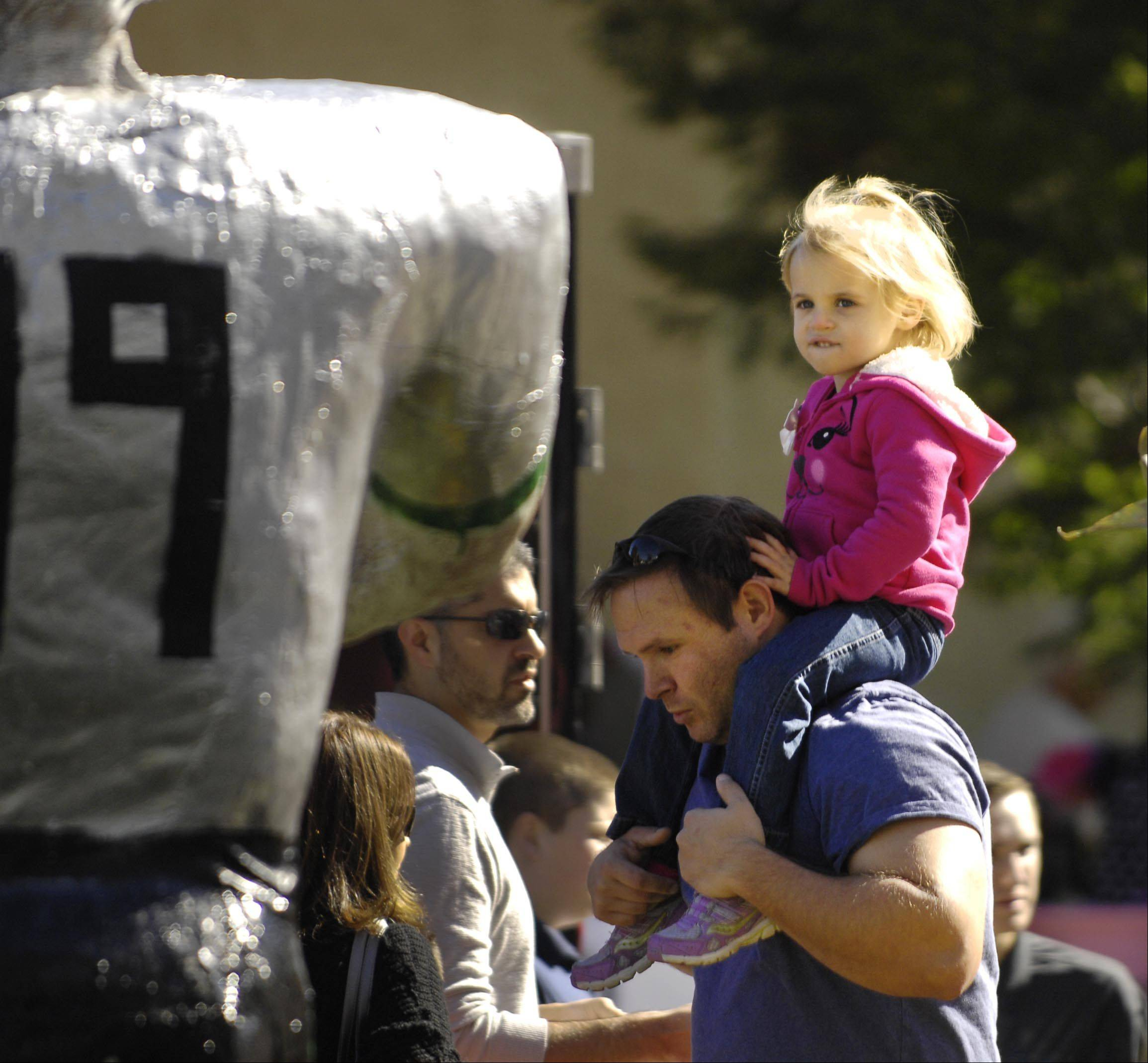 Ruth Jezioro, 3, looks at a large football player scarecrow as she rides the shoulders of her uncle Dave Delach of Batavia on Sunday at the 28th annual St. Charles Scarecrow Festival.