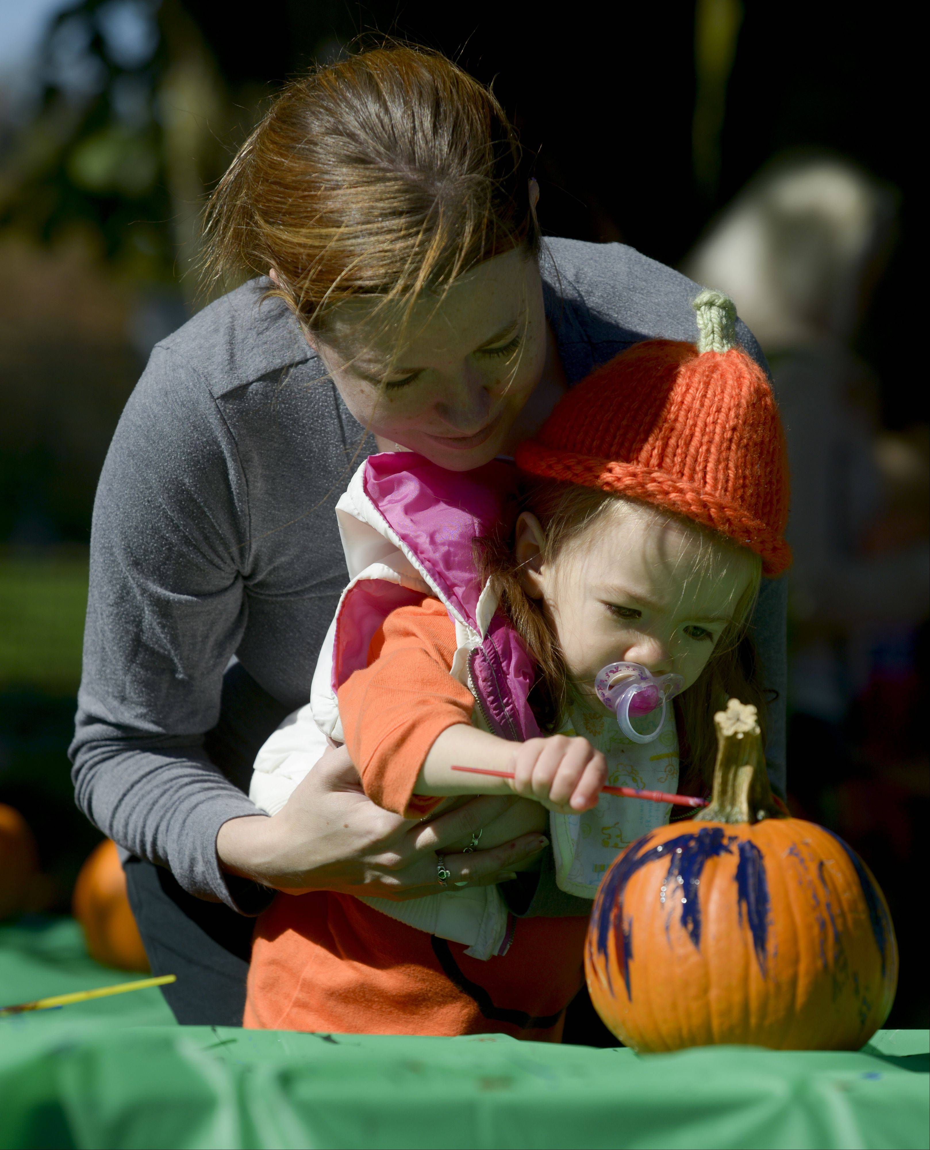 Jacqui Zurawski of Wheaton and her daughter Jozie, 2, paint a pumpkin during the Danada Fall Festival on Sunday in Wheaton.