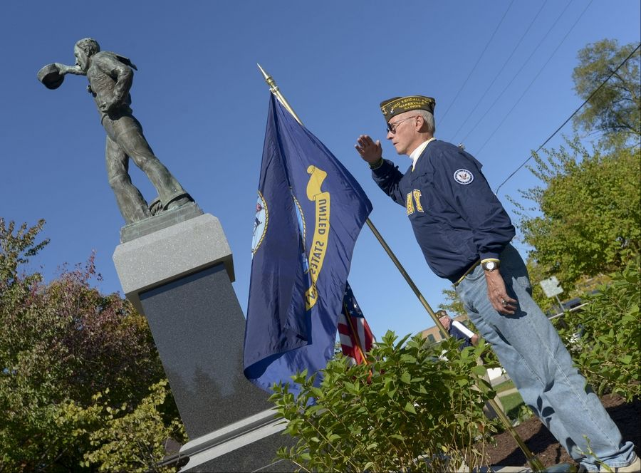 "The Navy flag waves as Navy veteran Lou Kueltzo gives a salute Sunday during the ""Spirit of the American Navy"" unveiling ceremony in Burlington Square Park in Naperville. ""Today is just another impressionable moment in my life as a U.S. Navy veteran,"" he said."
