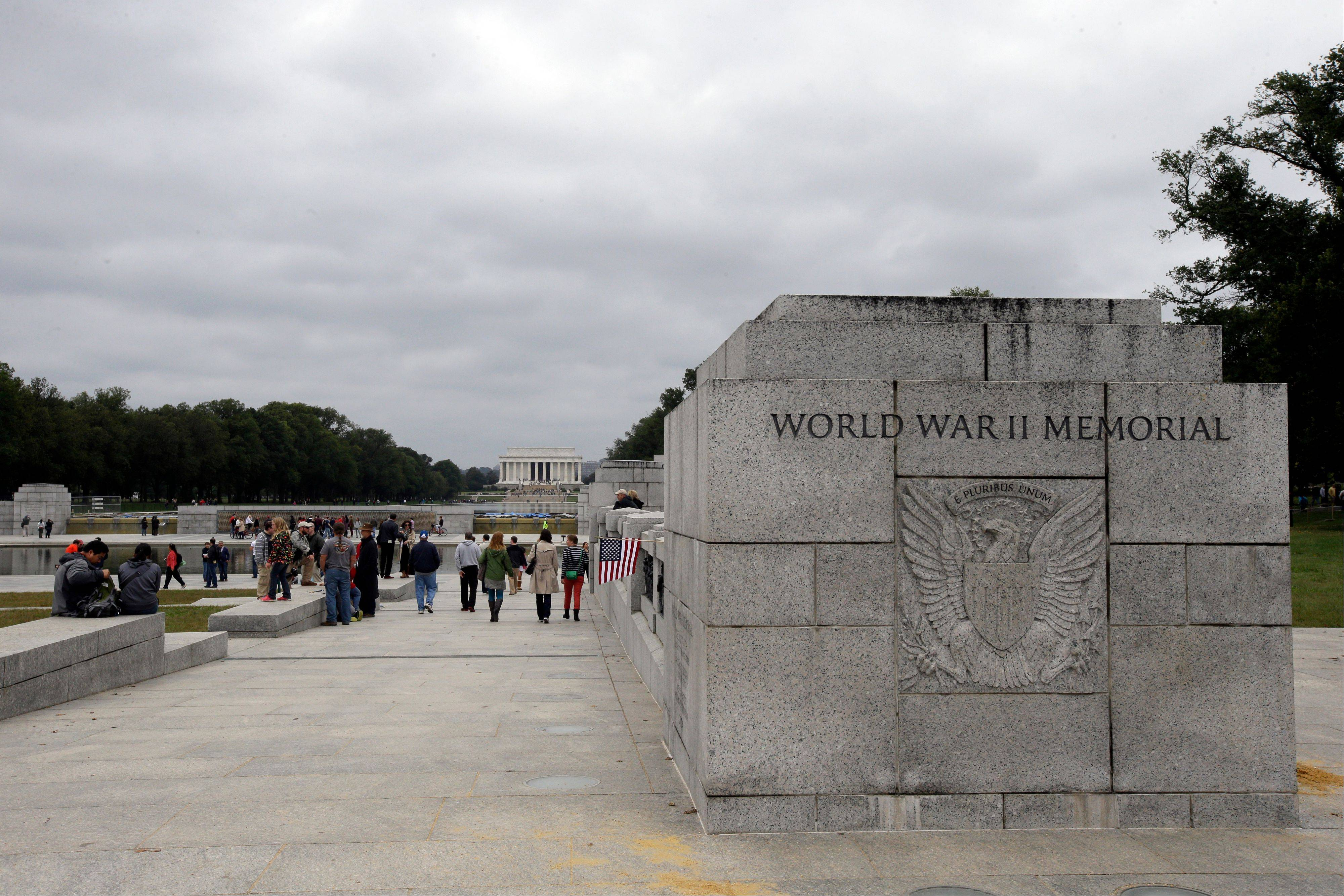 People walk around the World War II Memorial and the Lincoln Memorial, seen in the background, Sunday in Washington. The WWII memorial has been closed due to the government shutdown. Access barriers to the memorial site were moved aside by protesters.