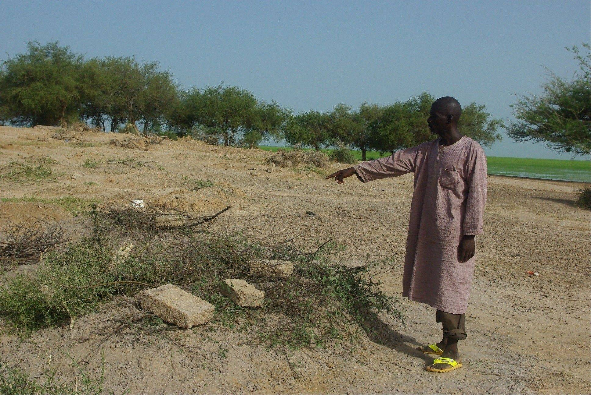Survivor Mahmoudou Ibrahim points out the graves of his three children Sunday in the village of Bouri, Mali. The children were killed when the boat they were traveling on Friday broke apart and sank into the Niger River.