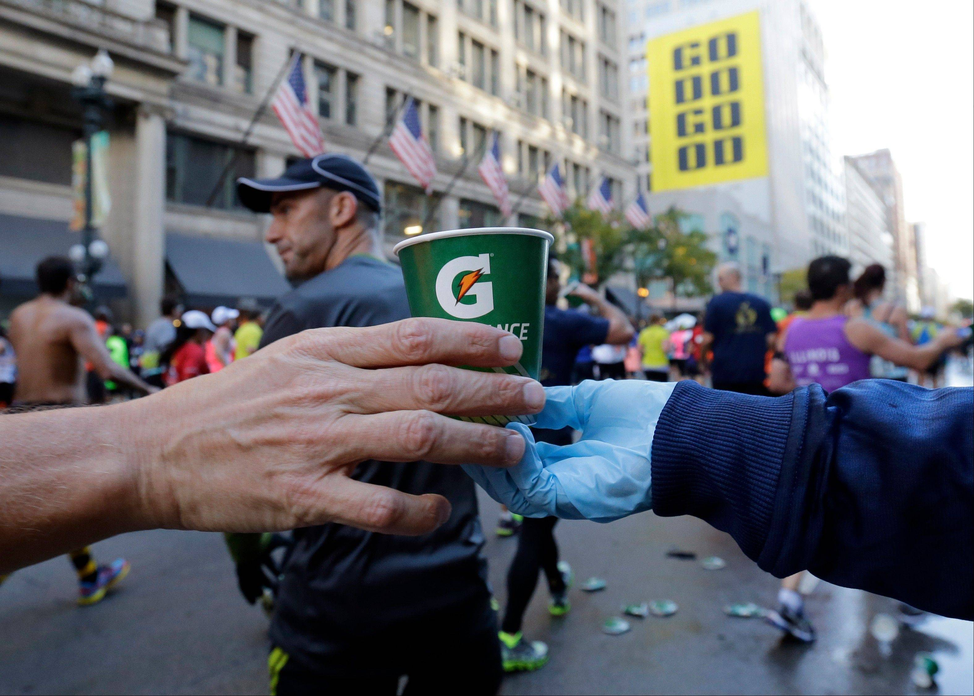 A runner grabs water at an aid station during the annual Chicago Marathon in Chicago, Sunday, Oct. 13, 2013.