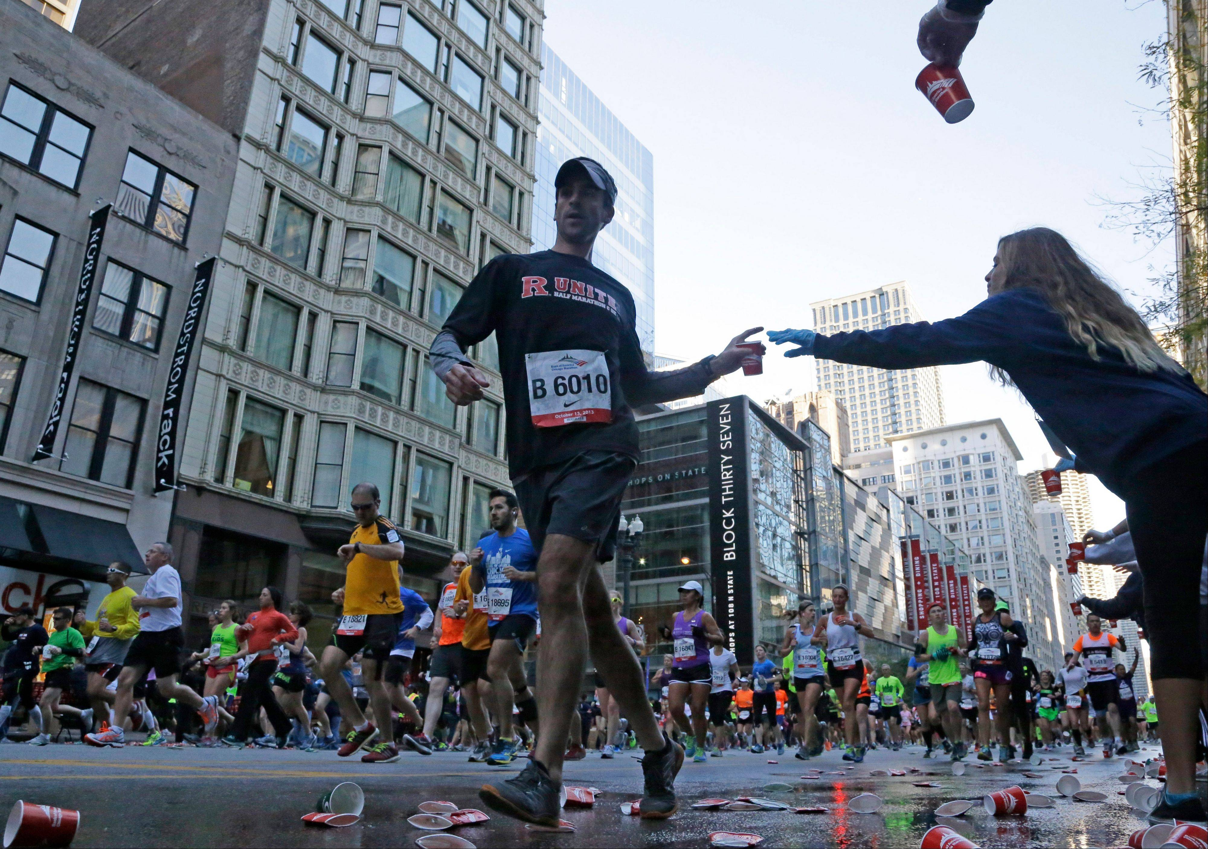 Runners grab water at an aid station during the annual Chicago Marathon in Chicago, Sunday, Oct. 13, 2013.