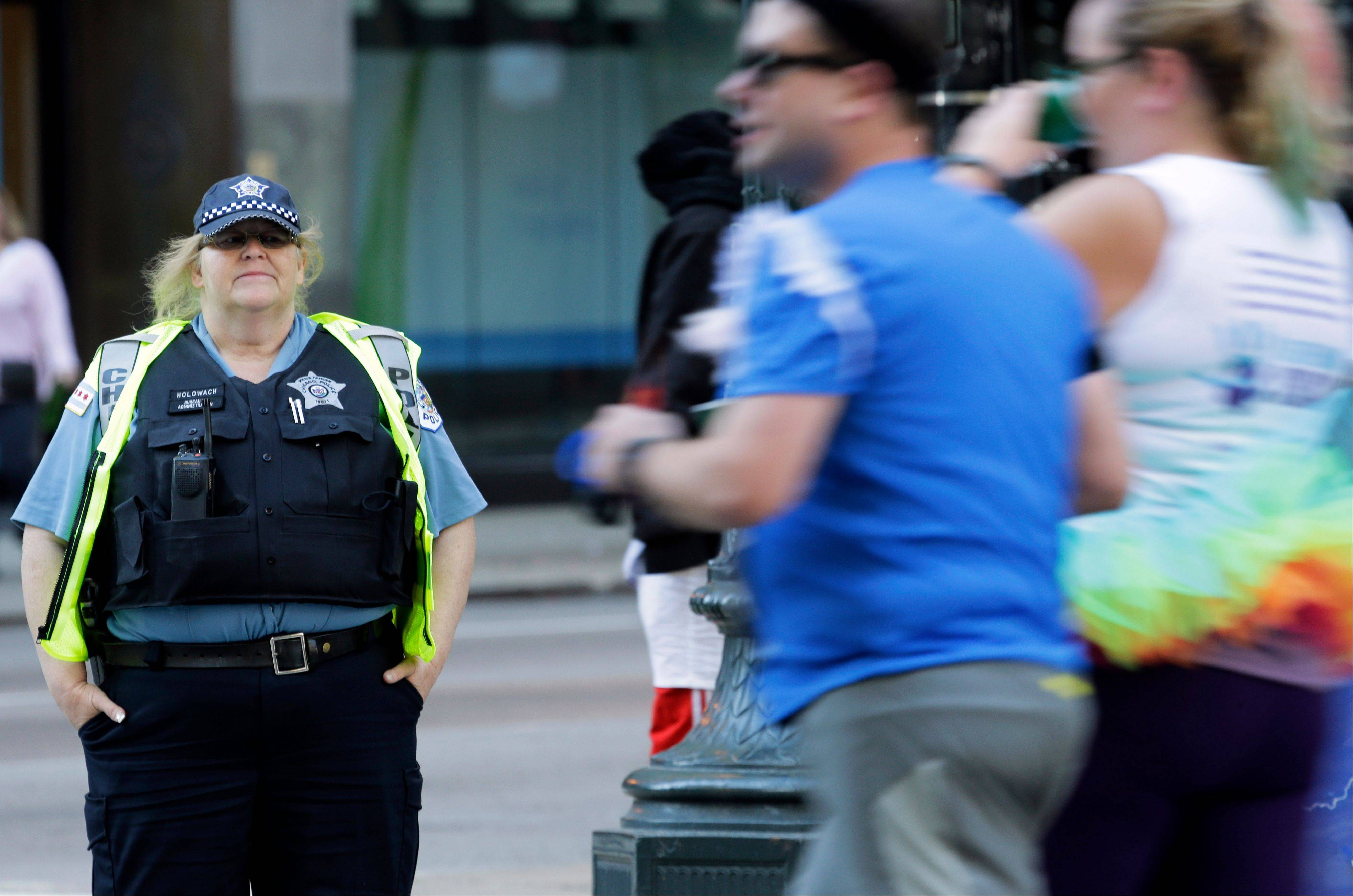 A Chicago police officer watches runners during the annual Chicago Marathon in Chicago, Sunday, Oct. 13, 2013. The marathon is the first World Marathon Major in the United States since the Boston Marathon bombings last April and will be the most closely watched.
