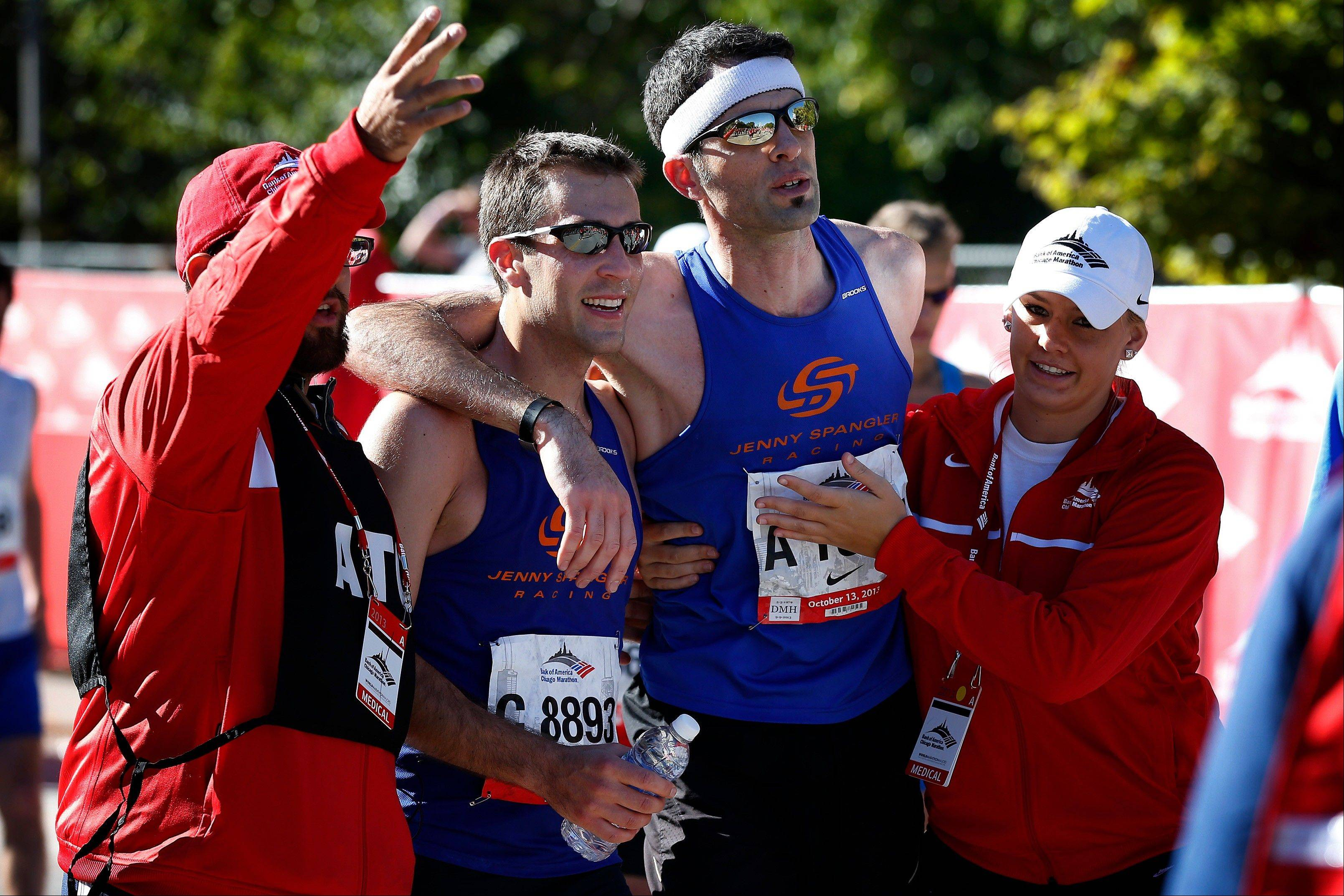 Lytle Smith, center left, of Evanston, Ill., and David Zeisler, center right, of Gurnee, Ill., are assisted at the finish line during the Chicago Marathon on Sunday, Oct. 13, 2013, in Chicago.