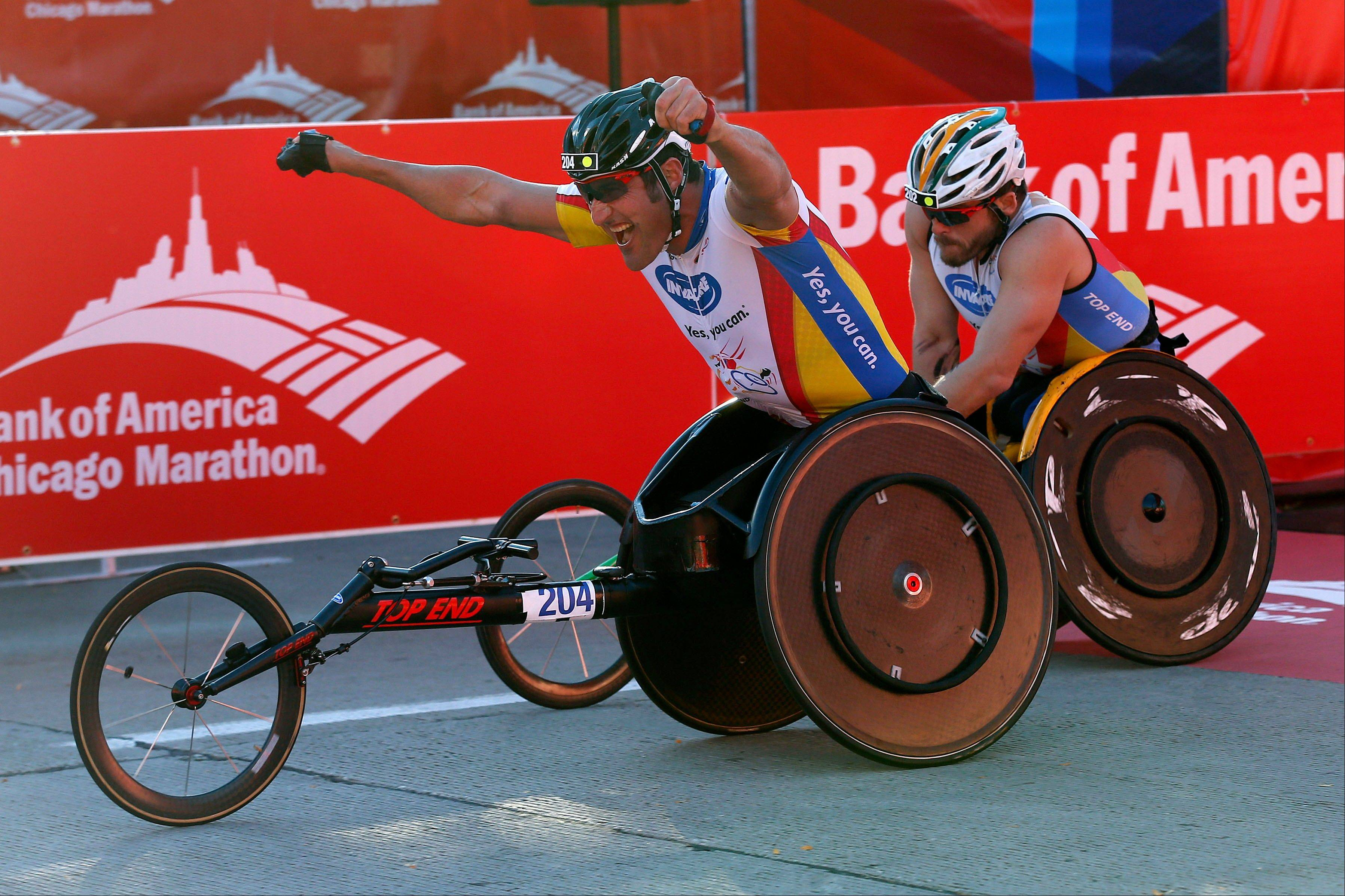 Ernst Van Dyke, left, of South Africa, edges out Kurt Fearnley, right, of Australia, to win the men's wheelchair division during the Chicago Marathon on Sunday, Oct. 13, 2013, in Chicago.