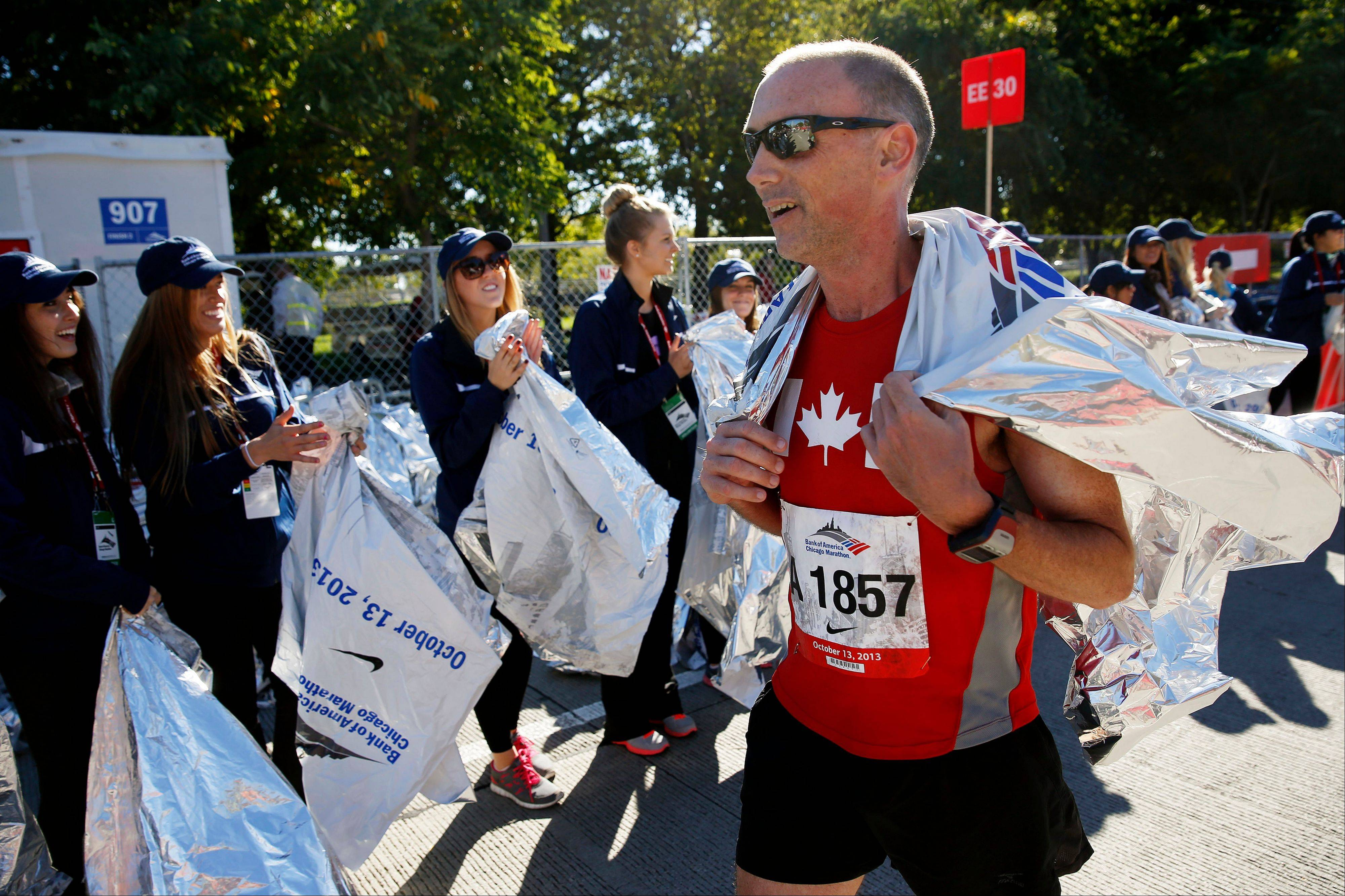 Michael Blois of Canada picks up a blanket after finishing the Chicago Marathon on Sunday, Oct. 13, 2013, in Chicago.