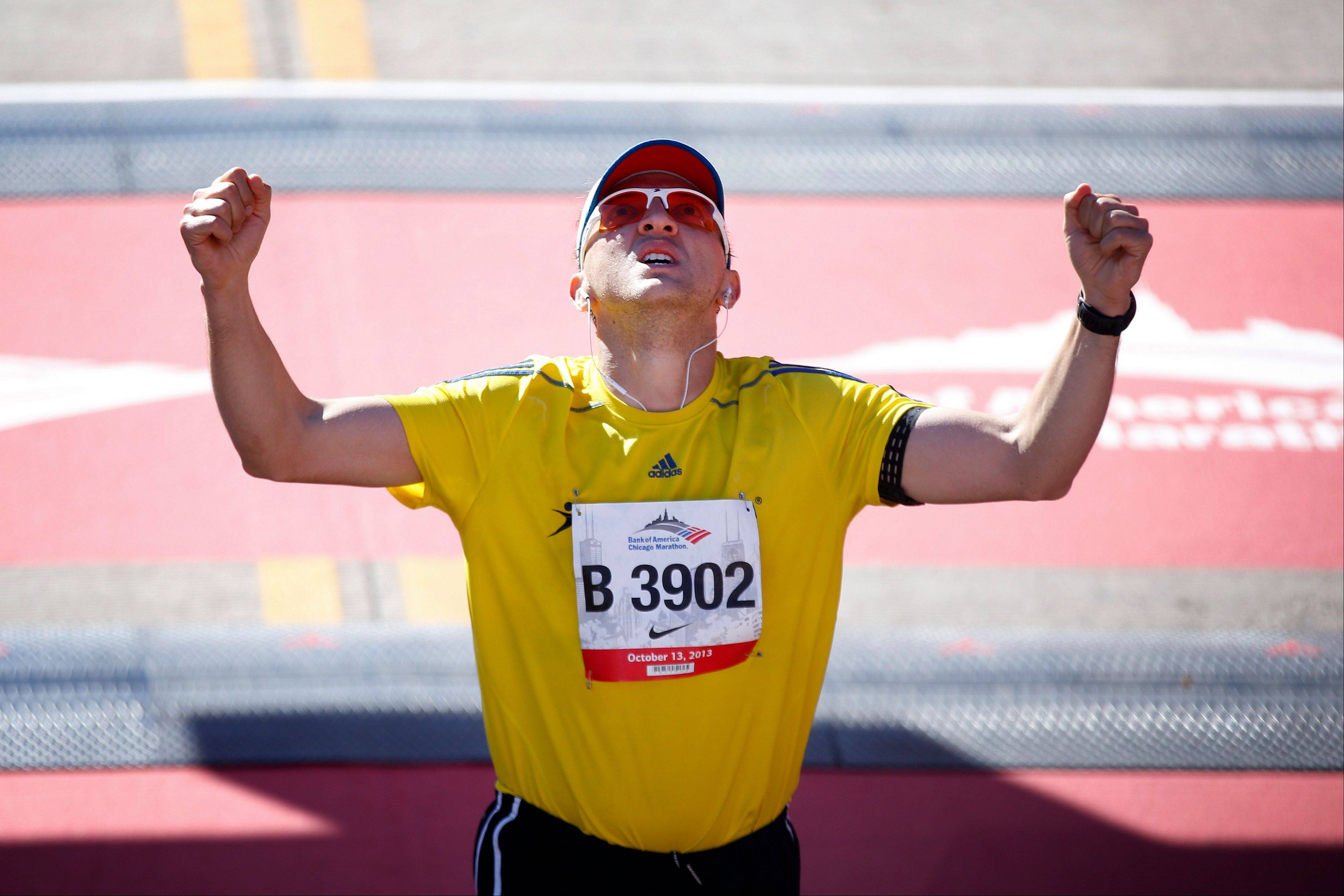 Lucas Perez of Columbia celebrates after crossing the finish line during the Chicago Marathon on Sunday, Oct. 13, 2013, in Chicago.